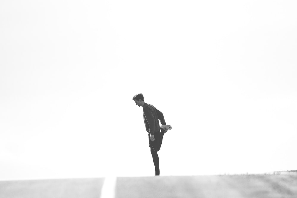 A black and white shot of a man stretching his right leg before running on the road