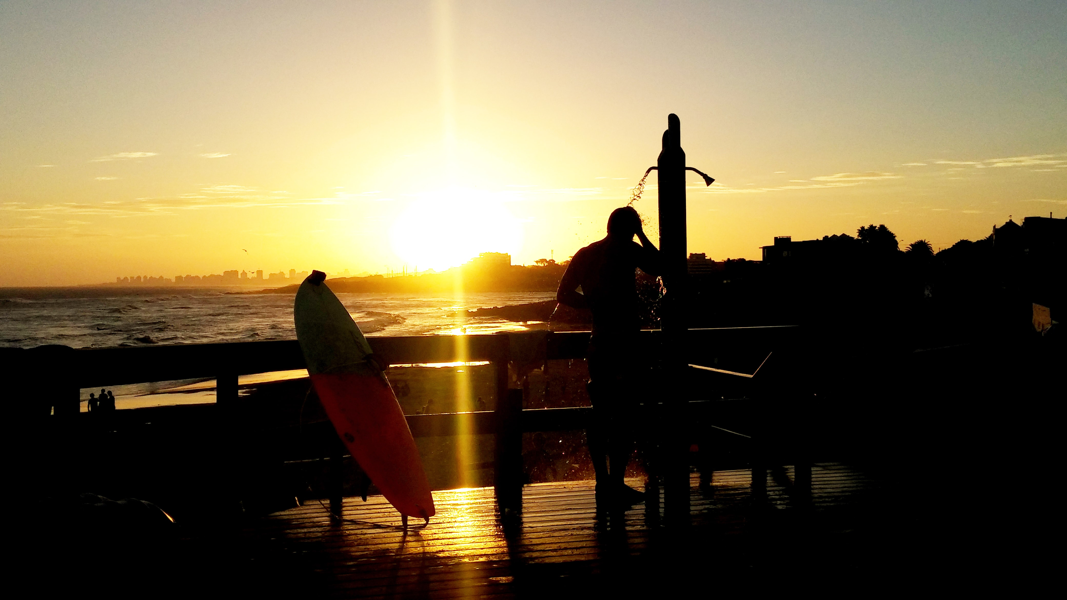 A silhouette of a man next to a propped up surfboard, looking out towards the sunset over the sea