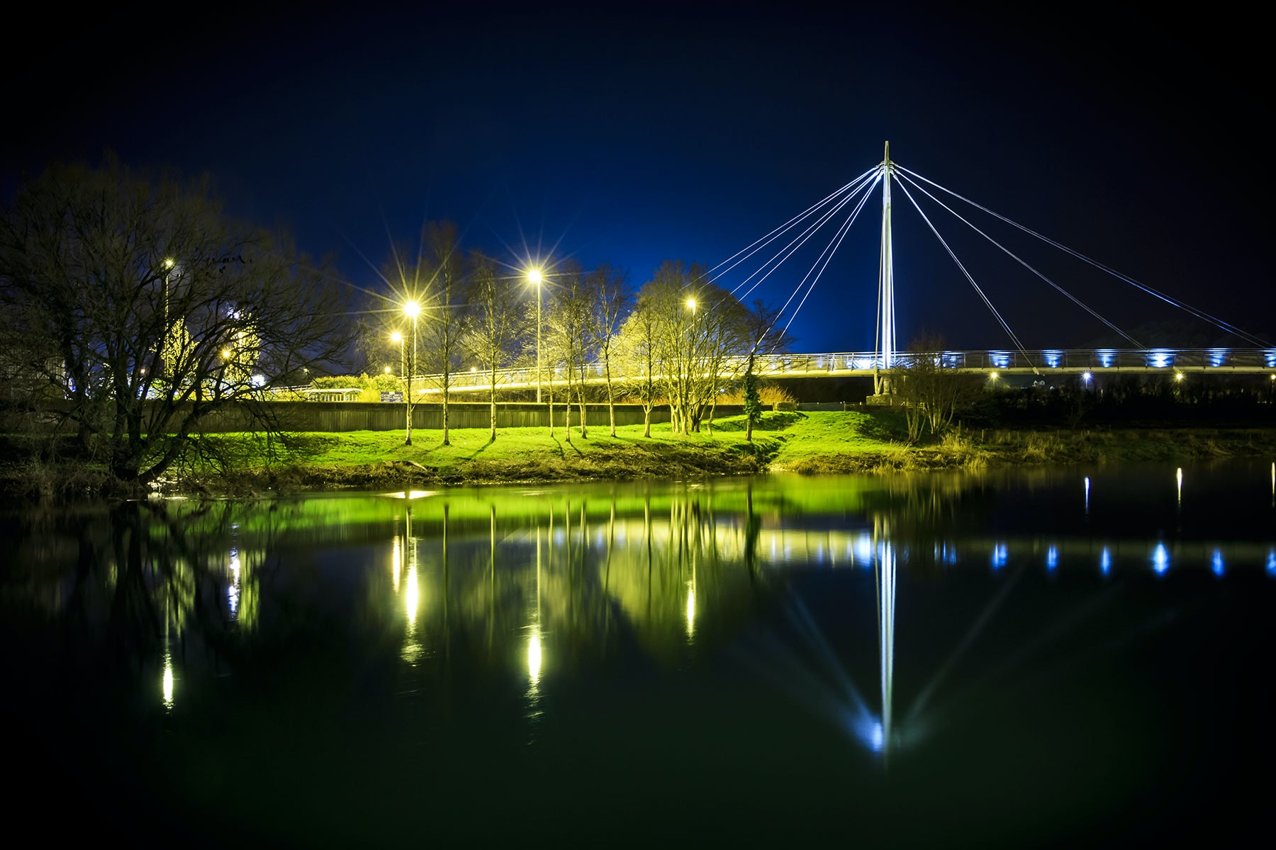Street lights and a suspension bridge reflect into a lake at night