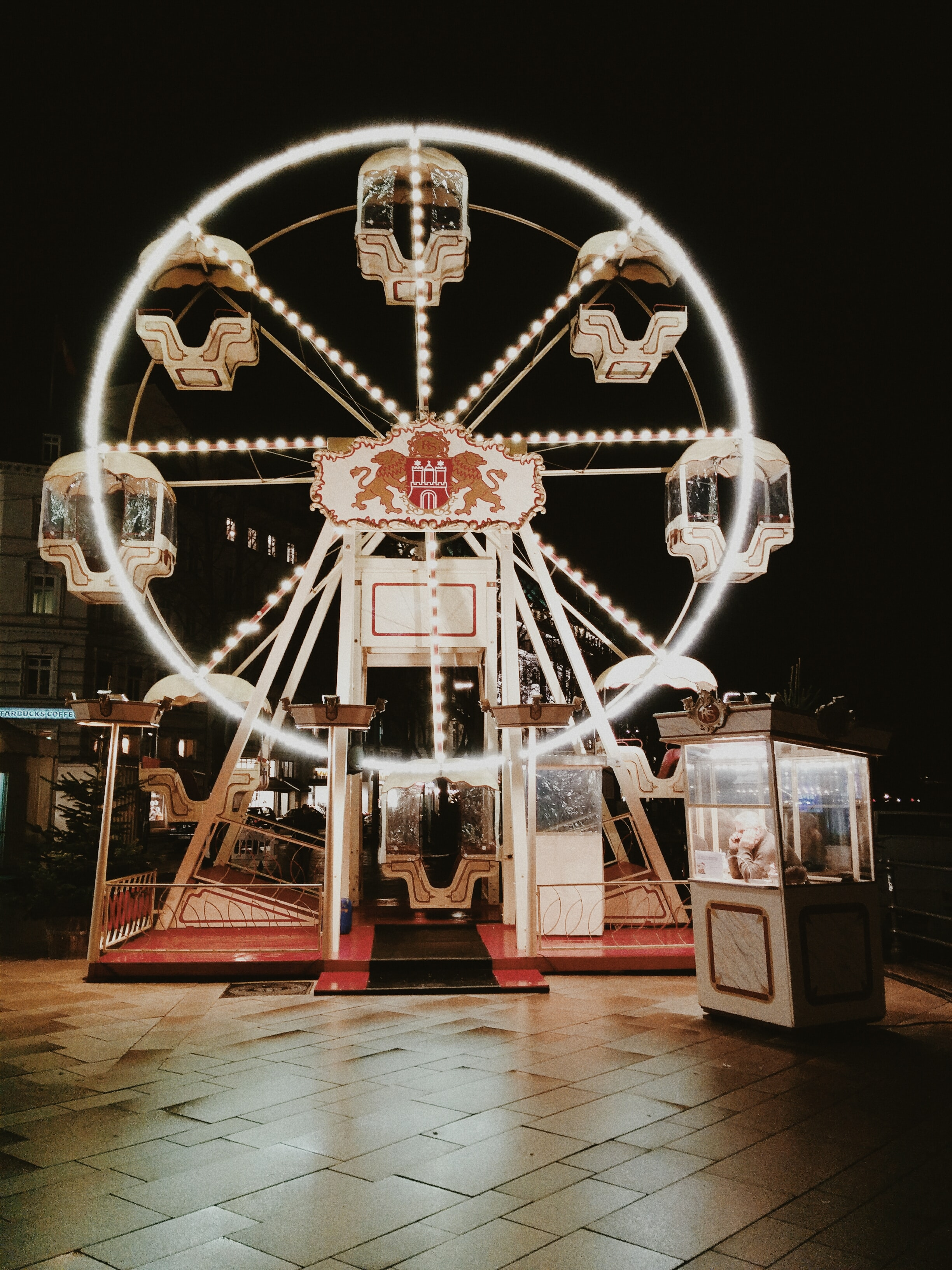 Small ferris wheel lit by bulbs at night with a person waiting in a booth