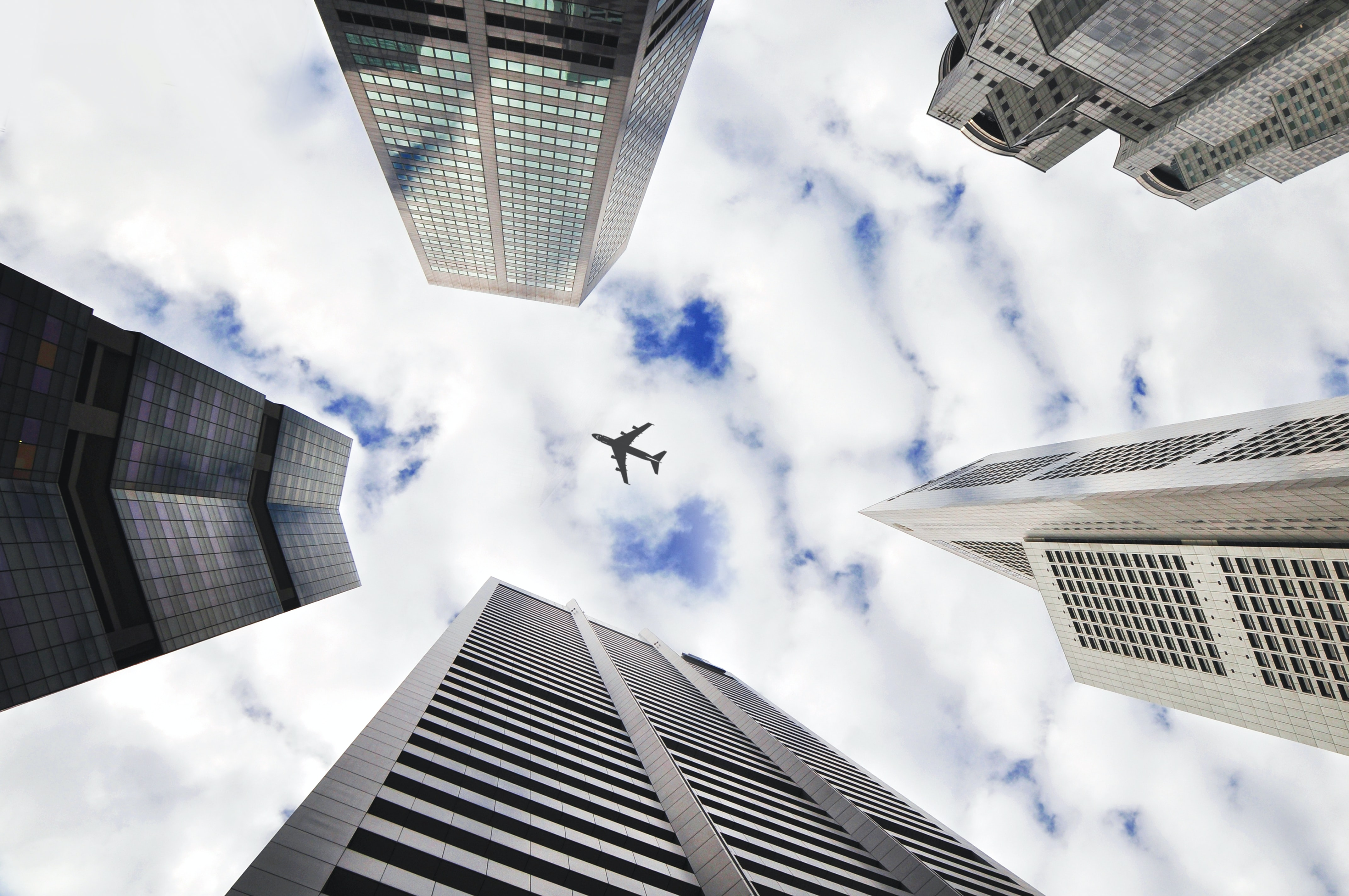 A low-angle shot of an airplane flying over tall skyscrapers