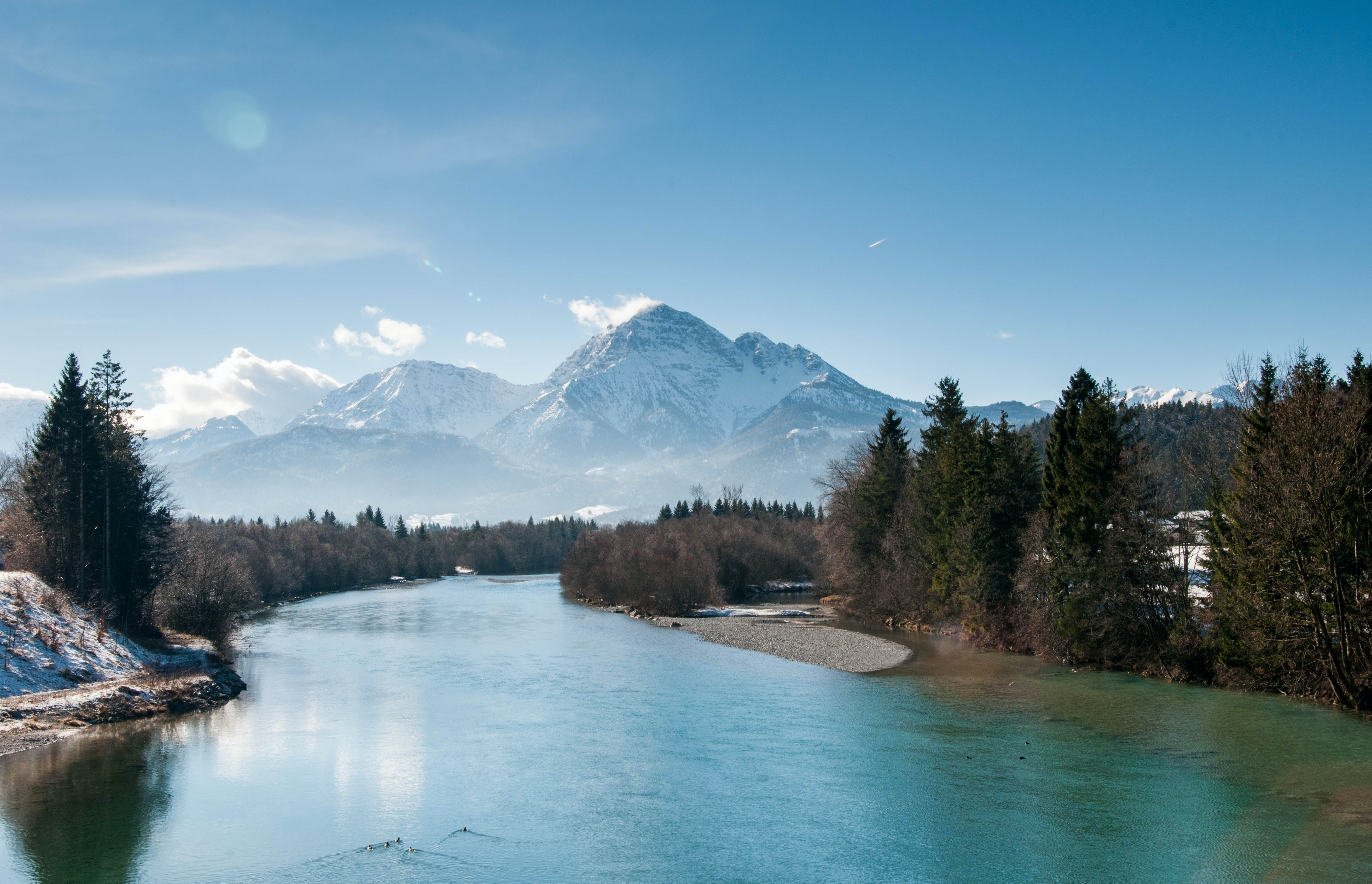 A scenic landscape with a bending river and snow-capped mountains in the distance
