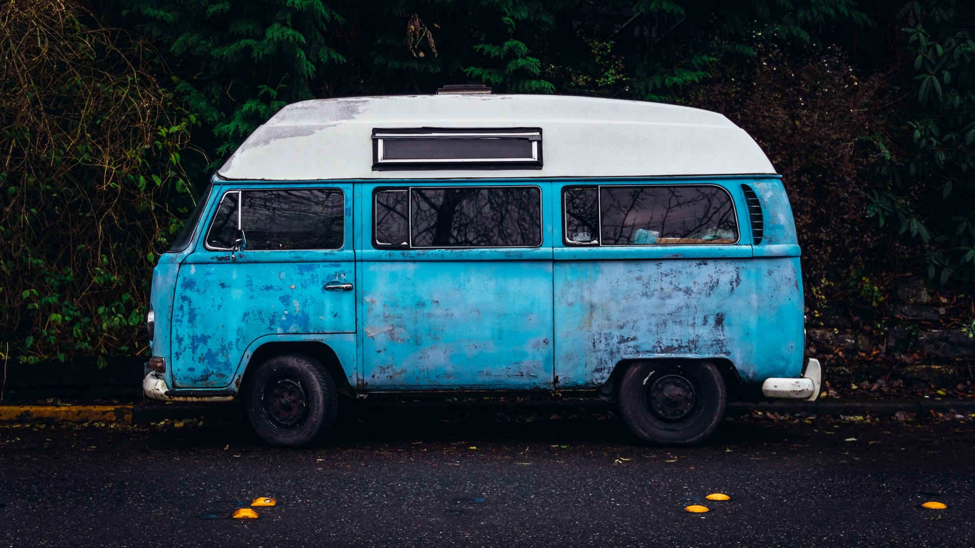 An old blue camper van with a white top parked on the side of the road