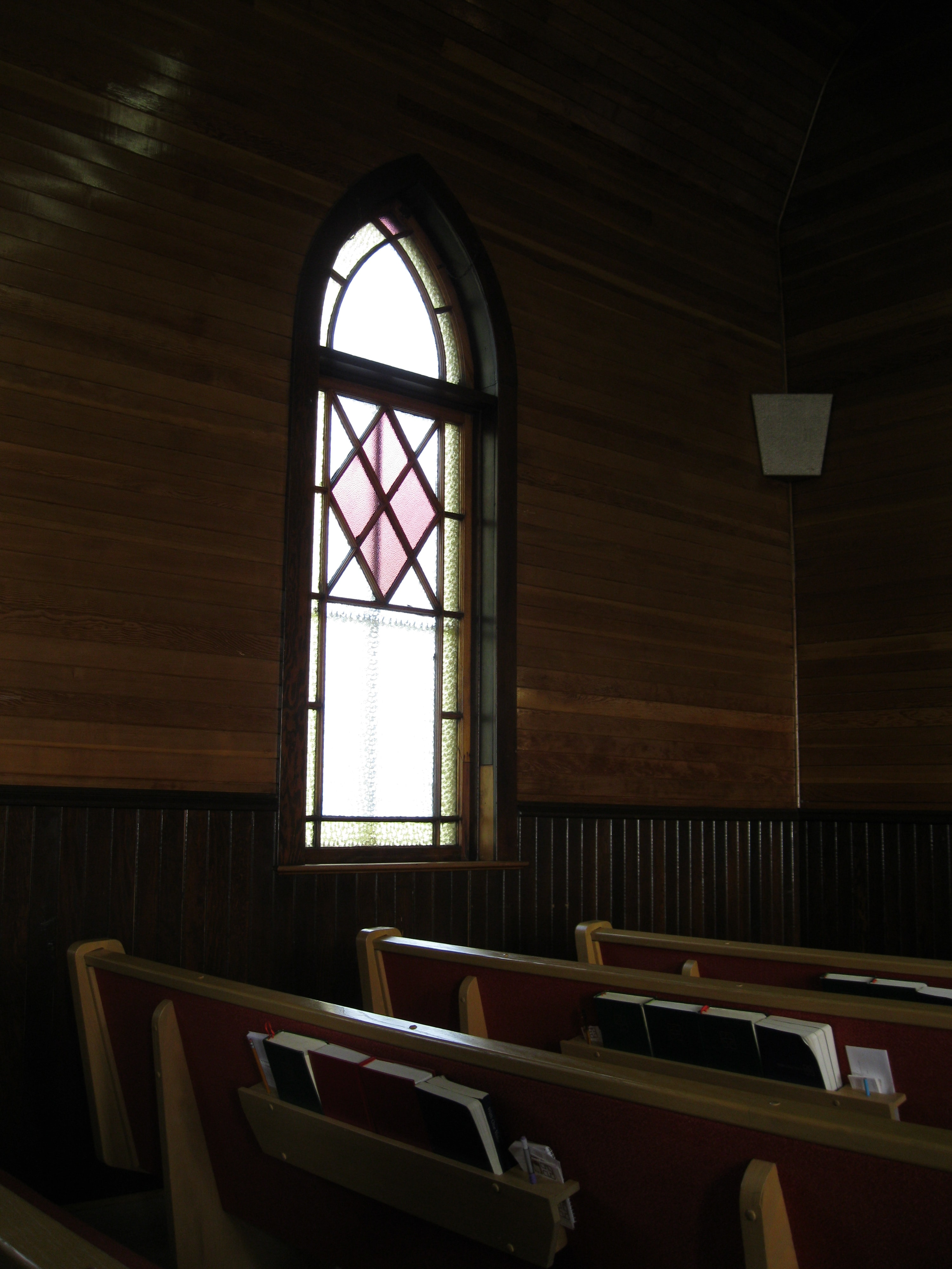 Basic light colored stained glass window, wooden interior, and pew with hymnbooks