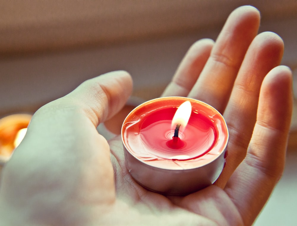 person holding red and white candle