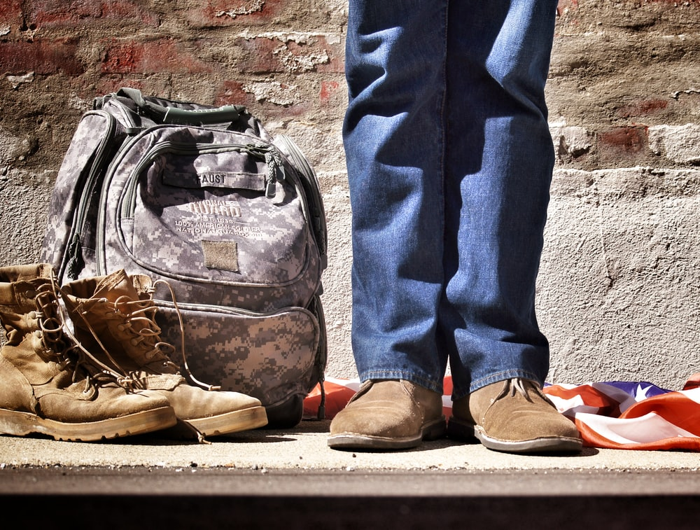 A person in the military standing next to their boots and backpack on a sidewalk