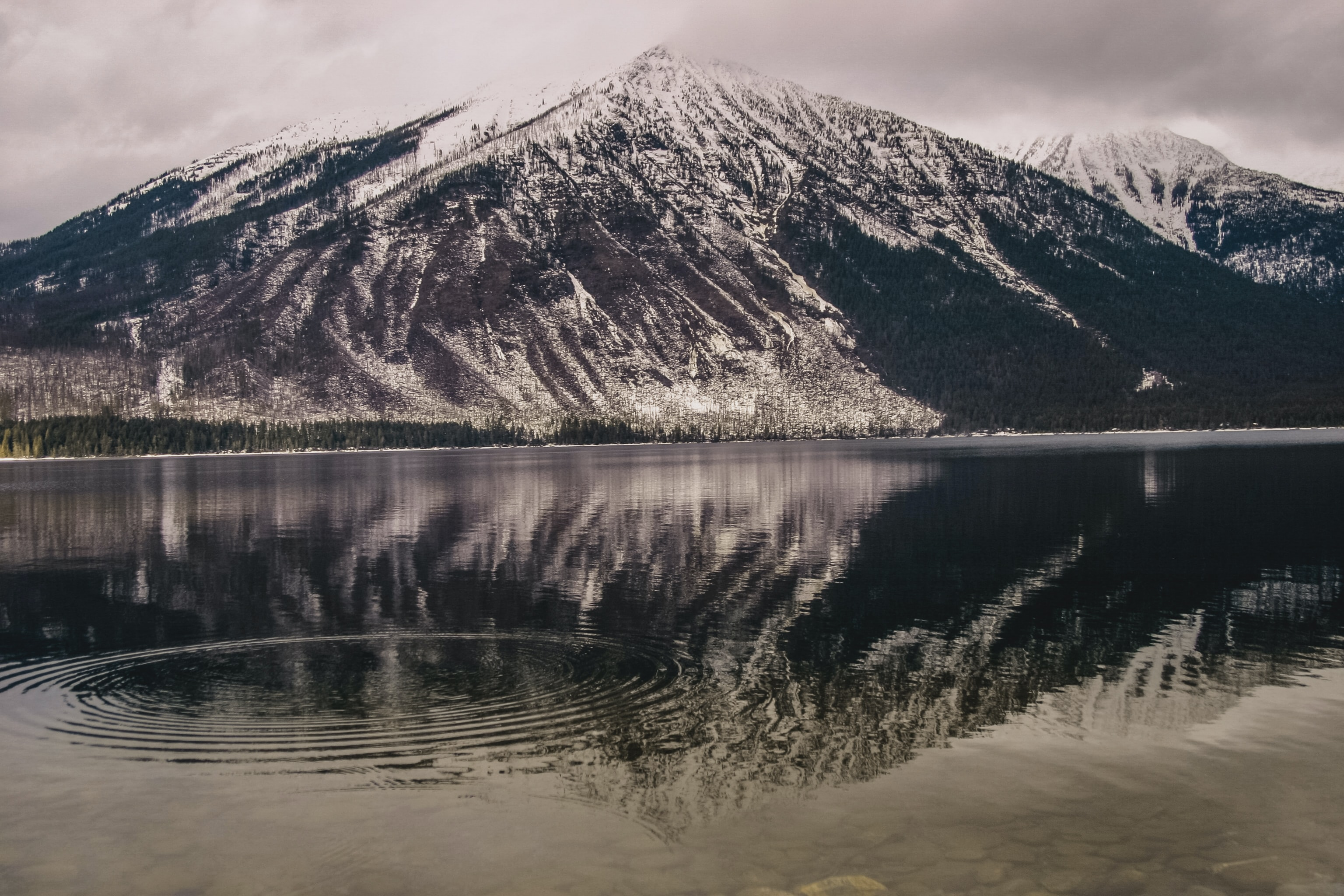 Ripples on the surface of a lake beneath a snow-capped mountain