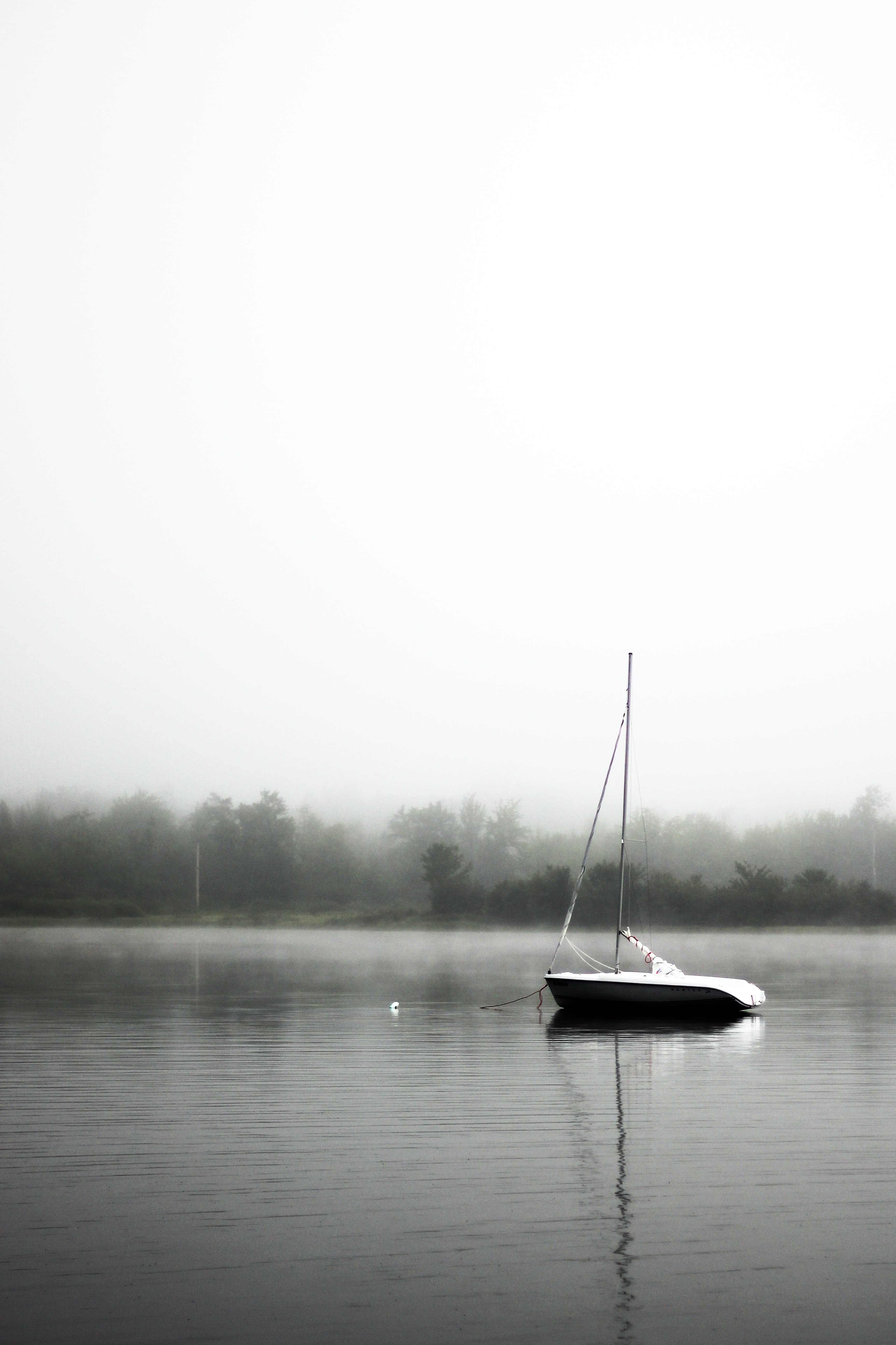 Sailboat sitting on a still lake on a foggy day