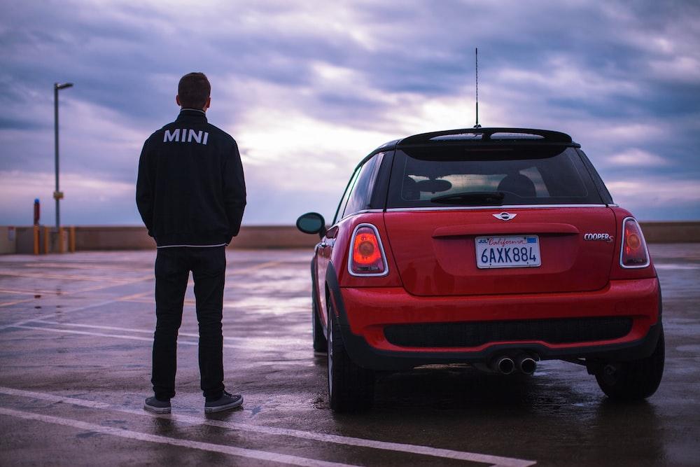 man standing red Mini vehicle during daytime