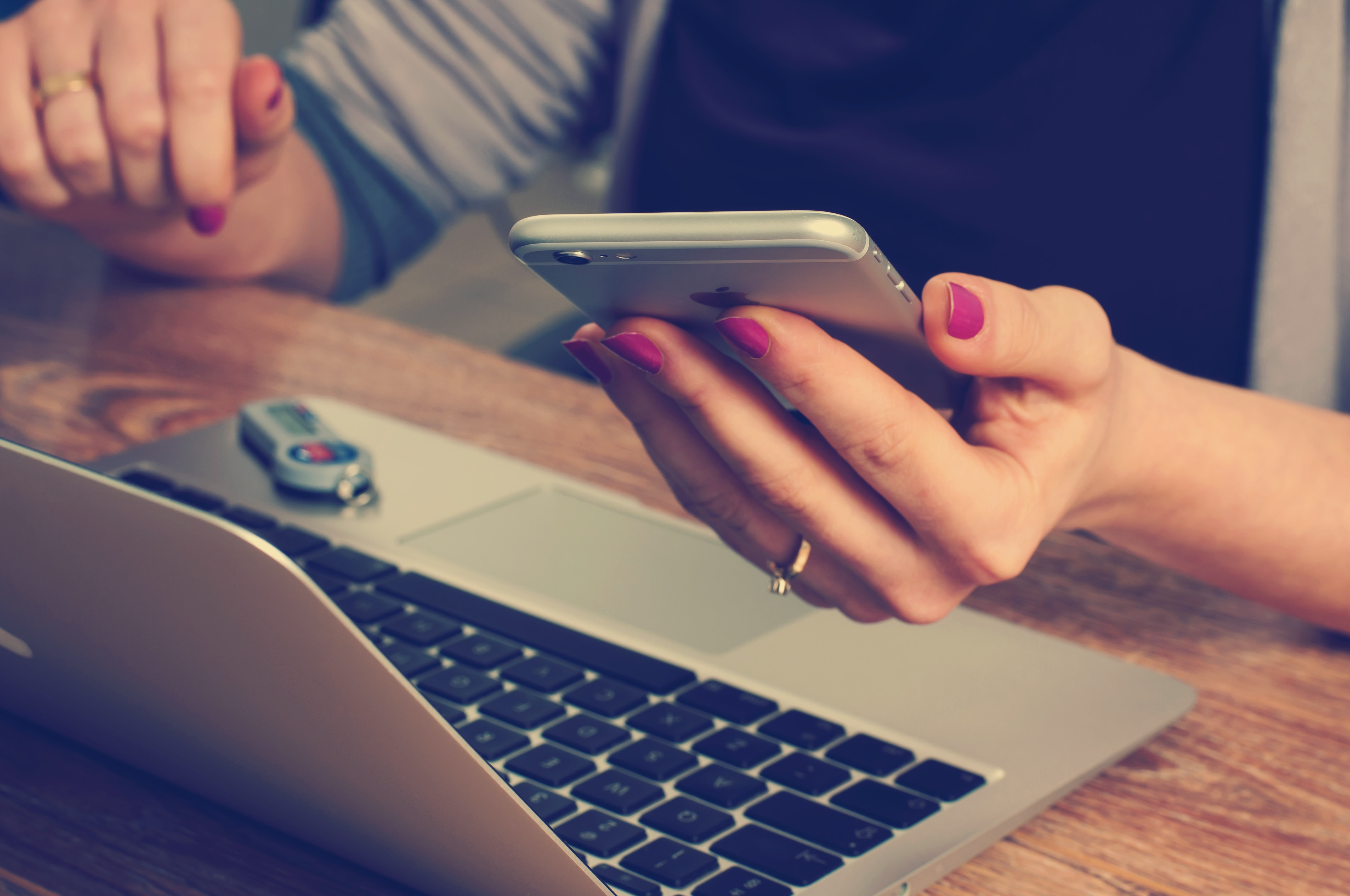 A woman's hand with a ring and a polished nail holding an iphone towards a laptop on a desk with a distant flash drive.
