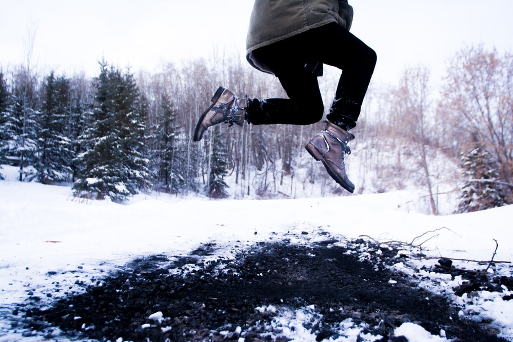 person jumping over black soil