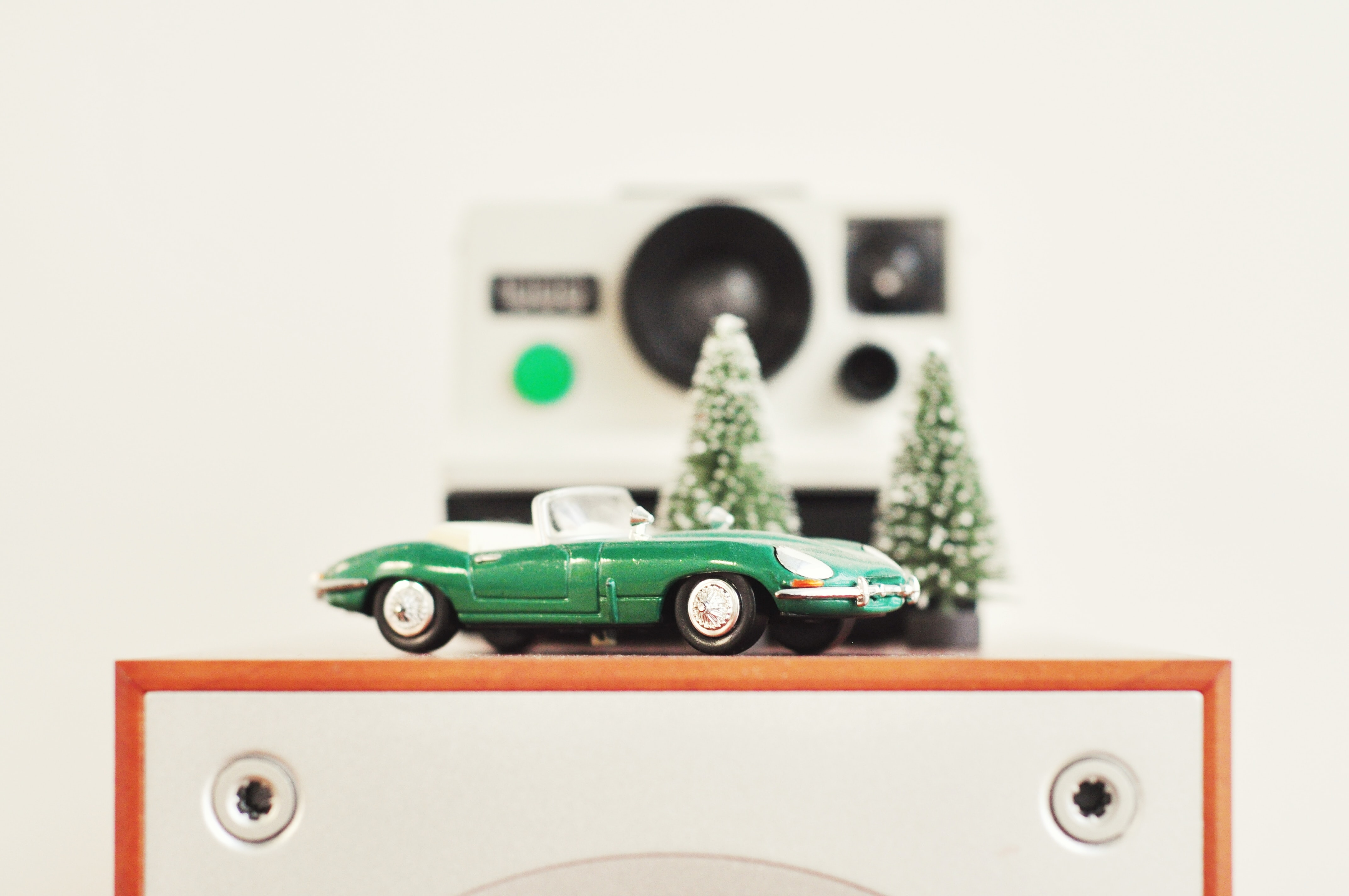 Toy car and trees in front of a polaroid camera.