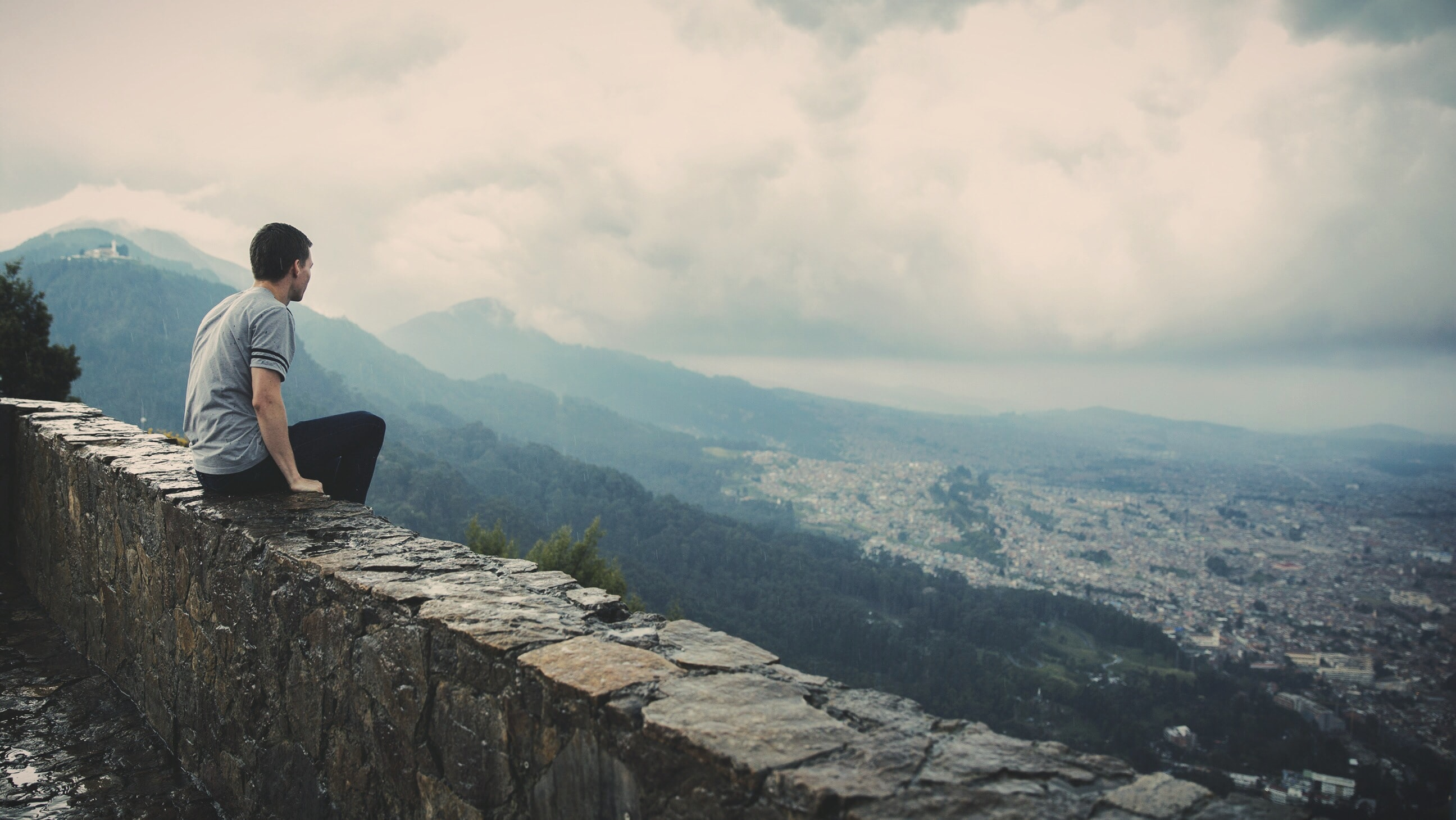 man sitting alone on concrete brick wall facing mountain and city under cloudy sky