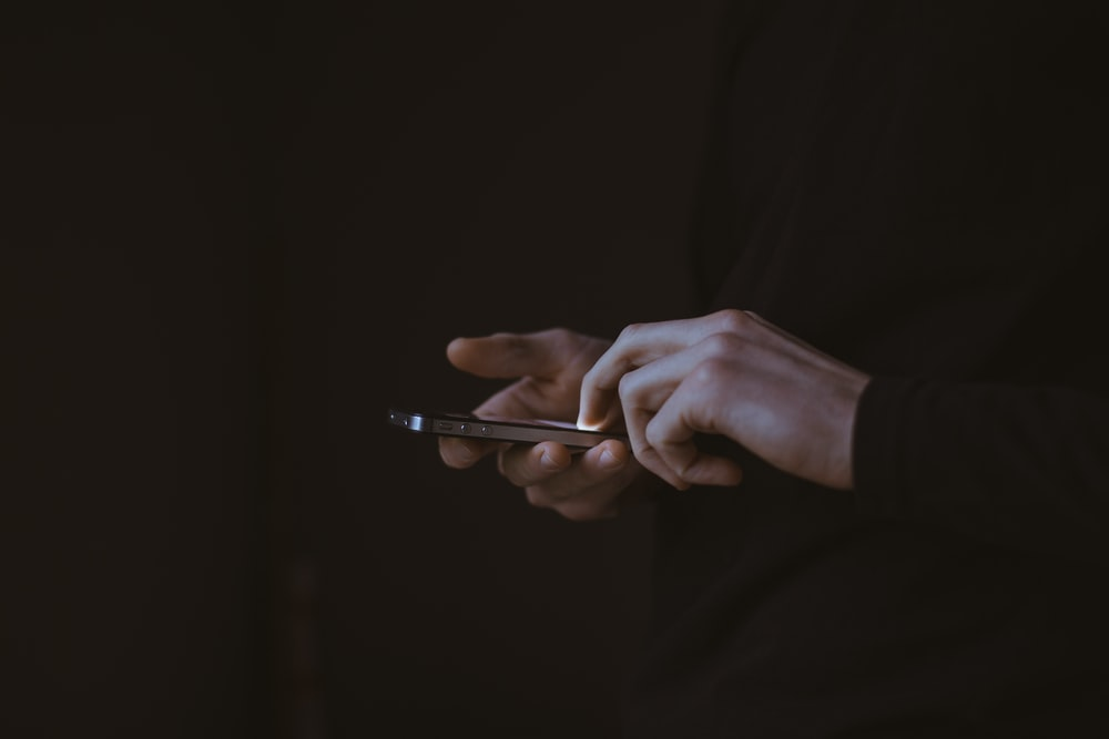 silhouette photo of person holding smartphone
