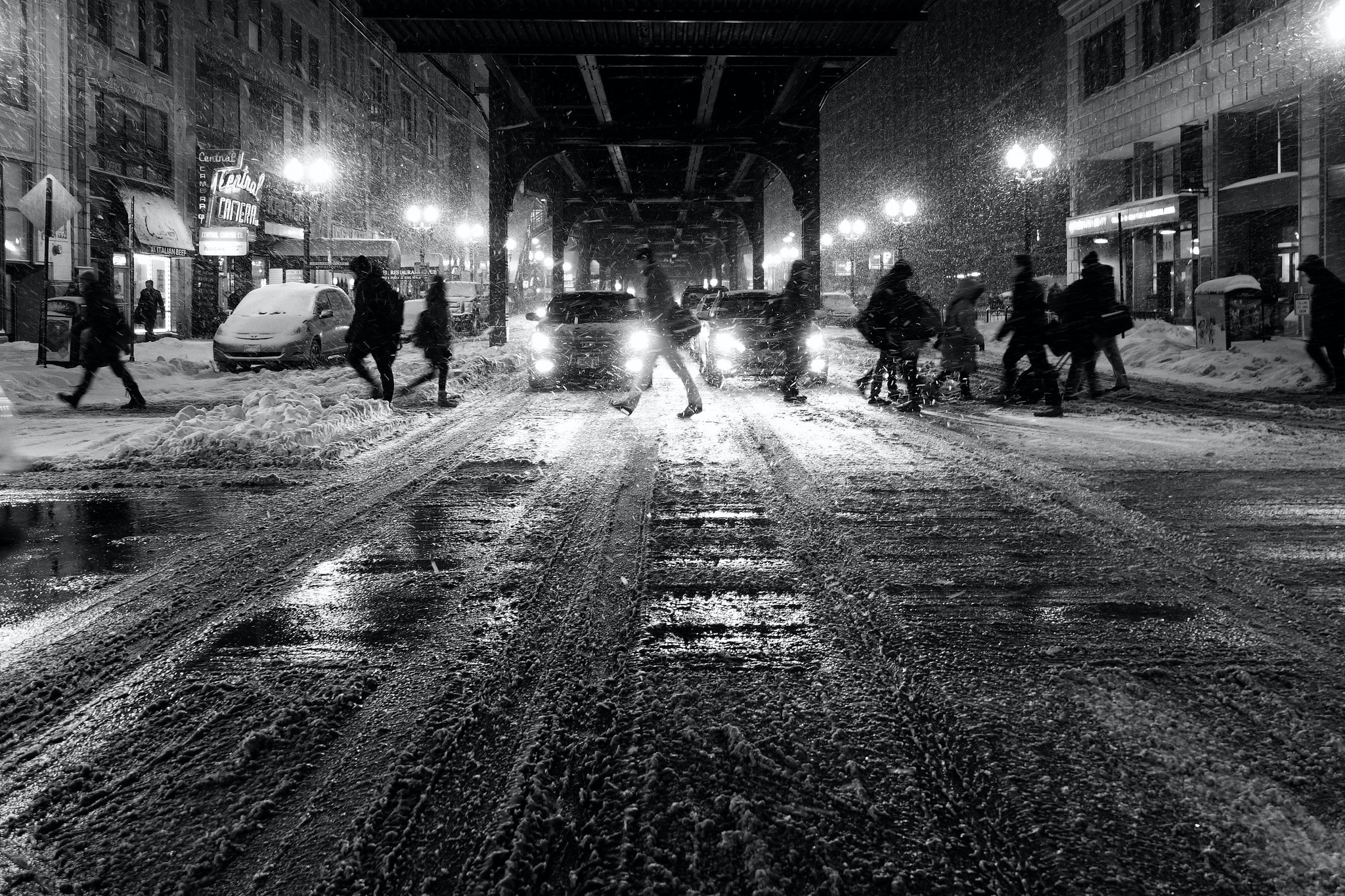 Black and white shot of people walking in city street slush with snow and cars