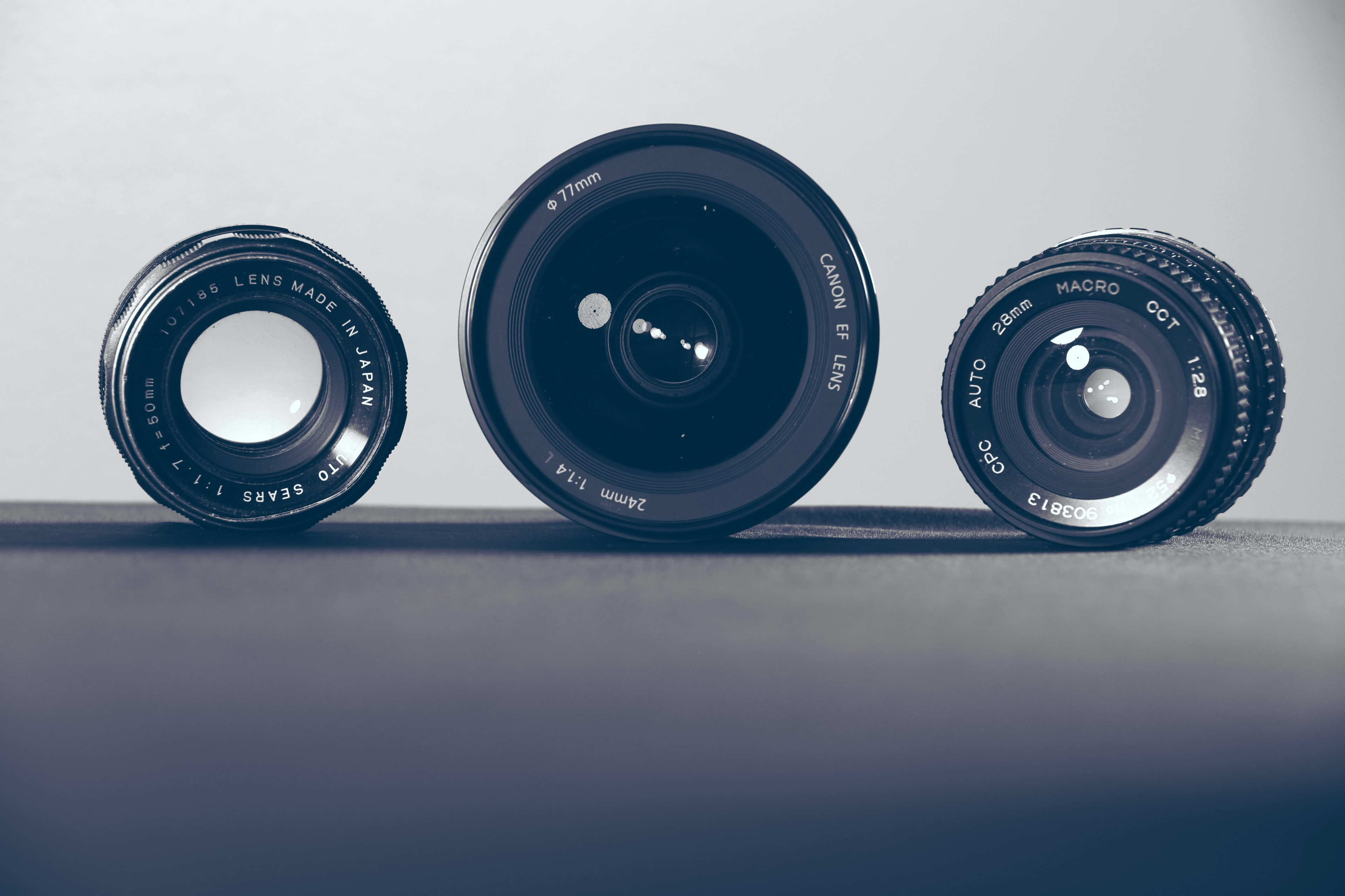 Three camera lenses on their sides on a dark surface