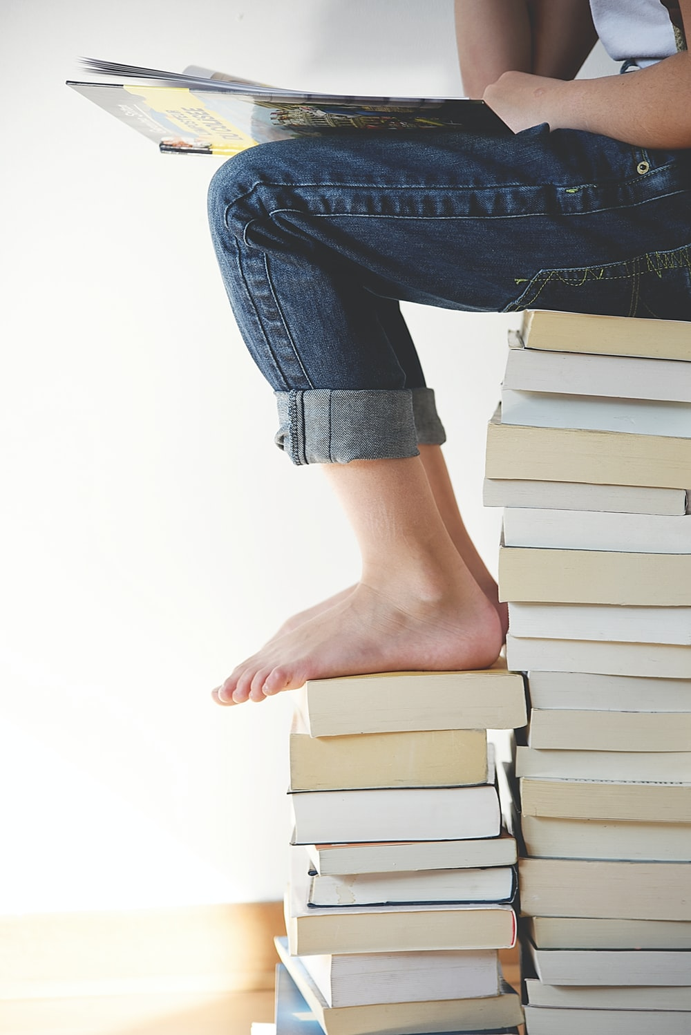 person sitting on stack of books while reading