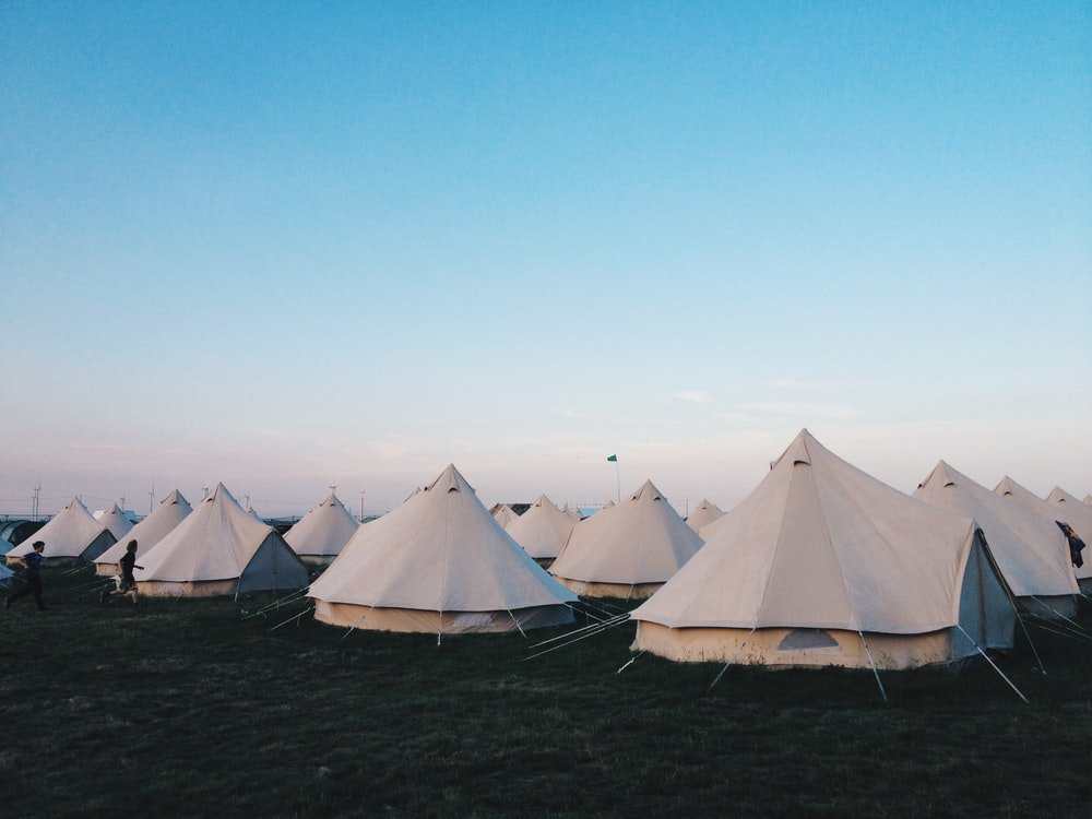 white tents on grass field under clear blue sky