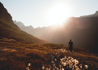 man walking beside the foot of the mountain during daytime