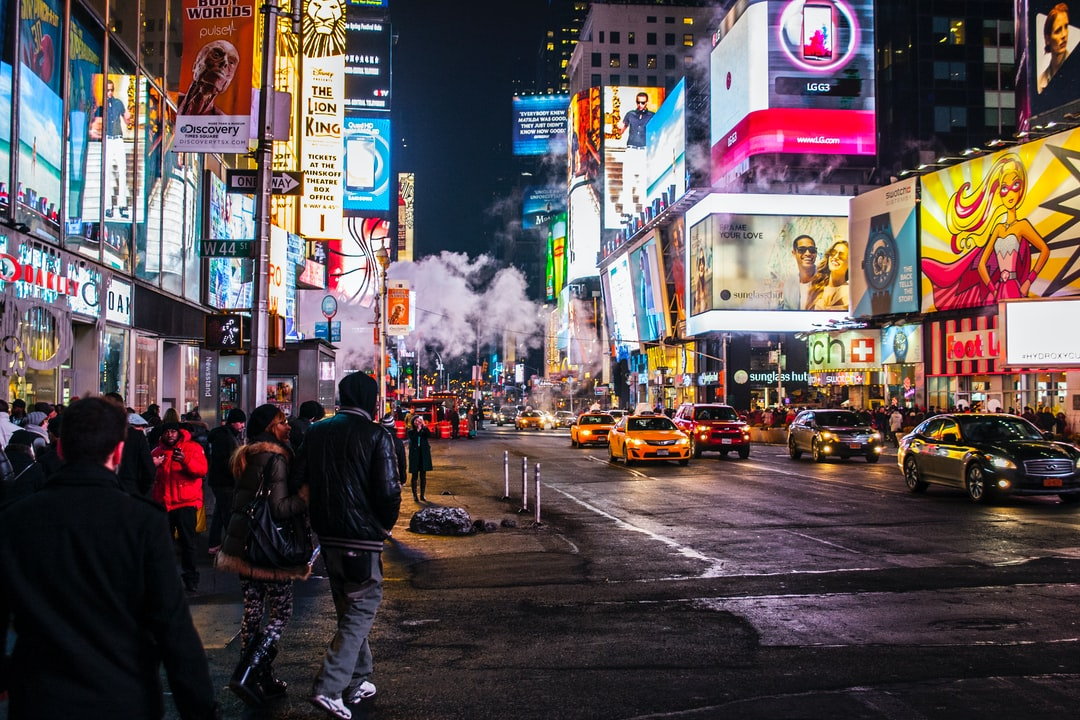 Pedestrians walk through the brightly lit Times Square at night while cars drive past