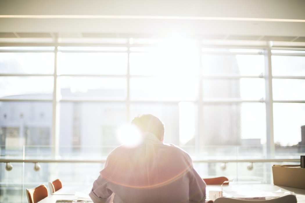image of man working at desk with light coming through window