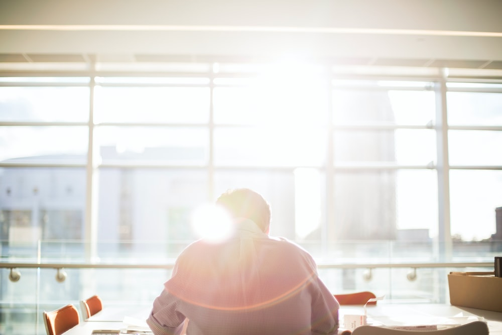 A man reading in an office directly sitting and facing towards the window flooded with rays of sunshine