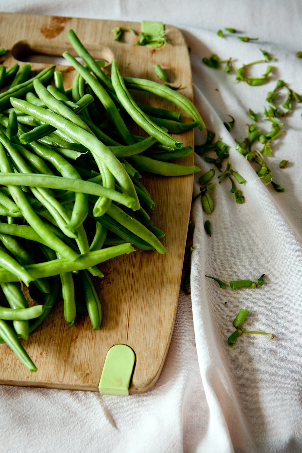 green peas on top of brown wooden chopping board