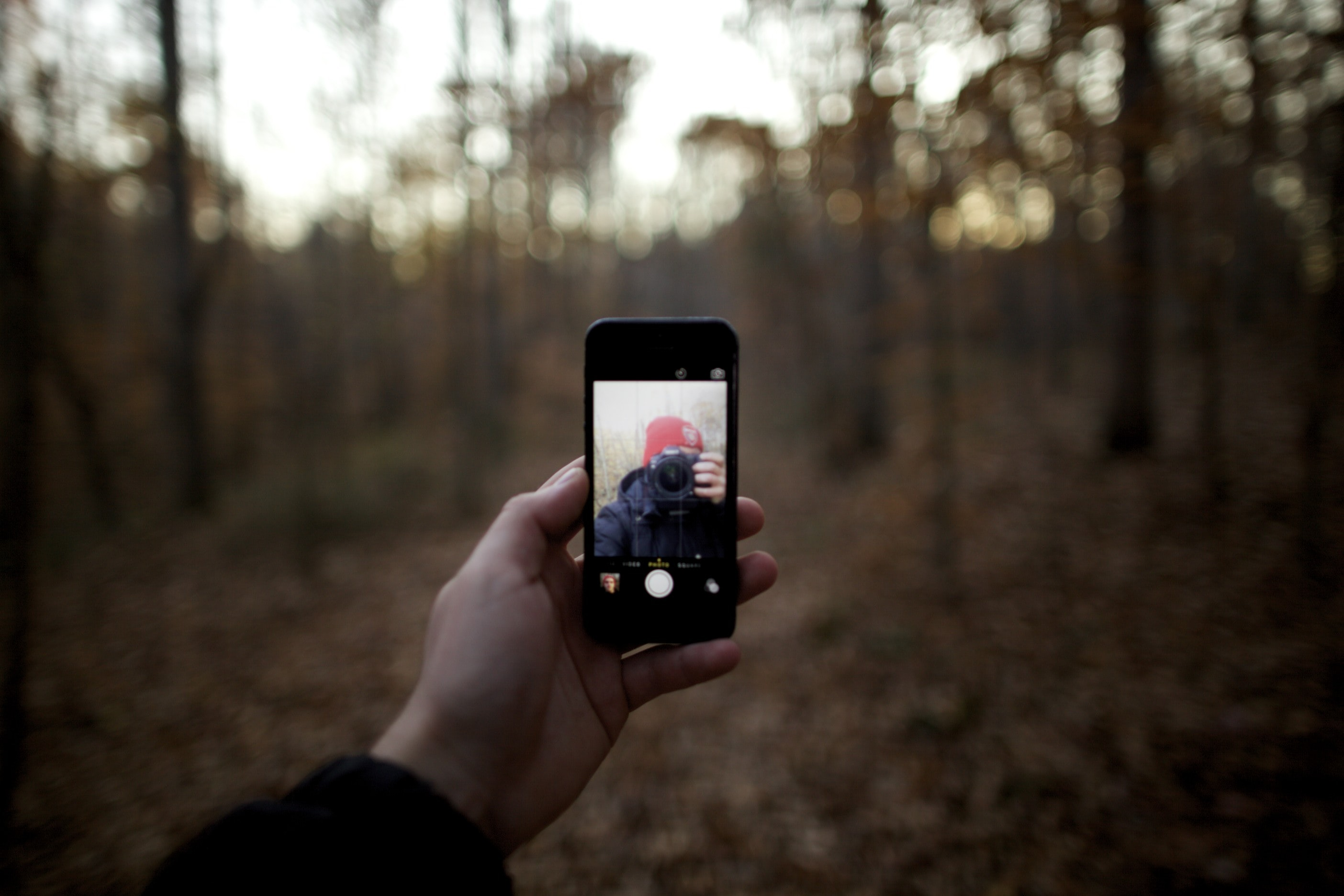 A young man holding out an iphone for a selfie alongside his camera in the woods