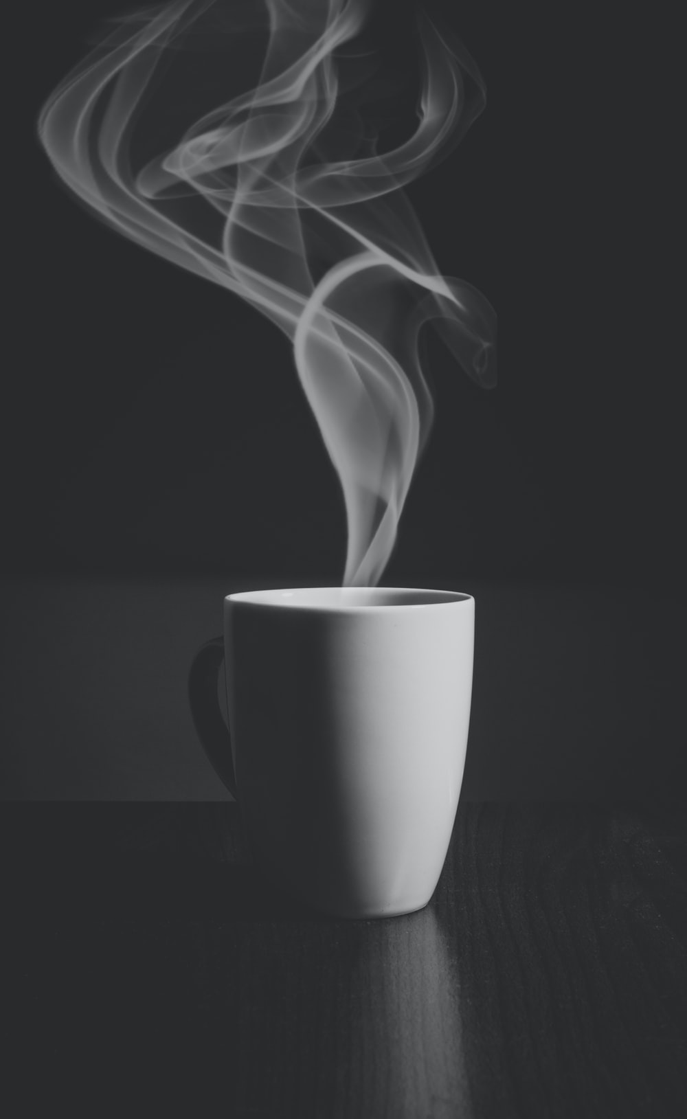 A hot drink in a white cup, with steam rising into the air.