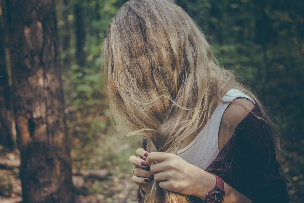 woman holding her hair in forest