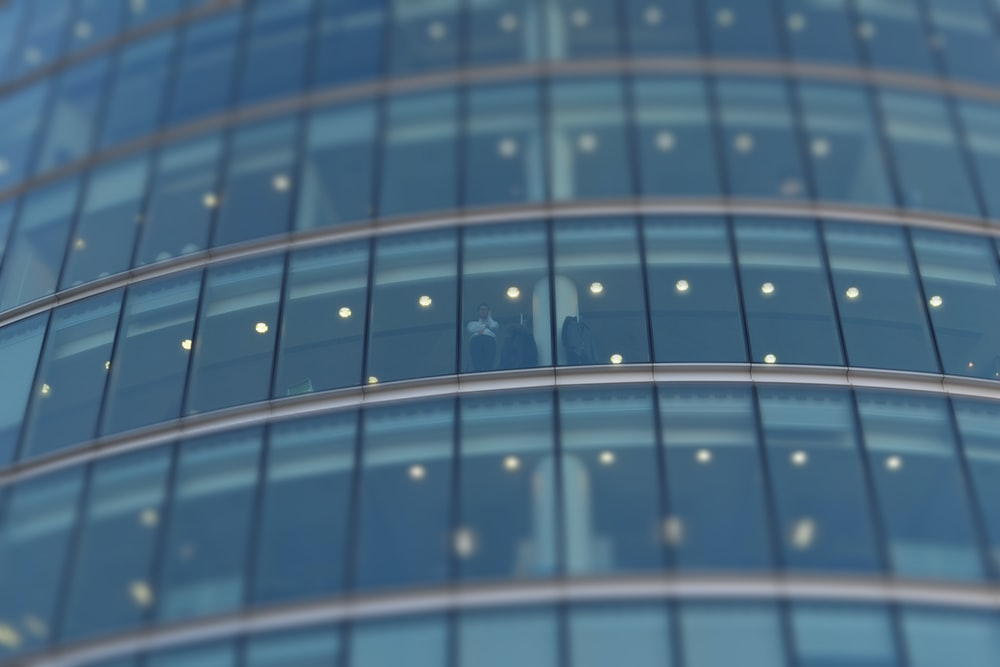 selective focus photograph of person standing near building glass curtain