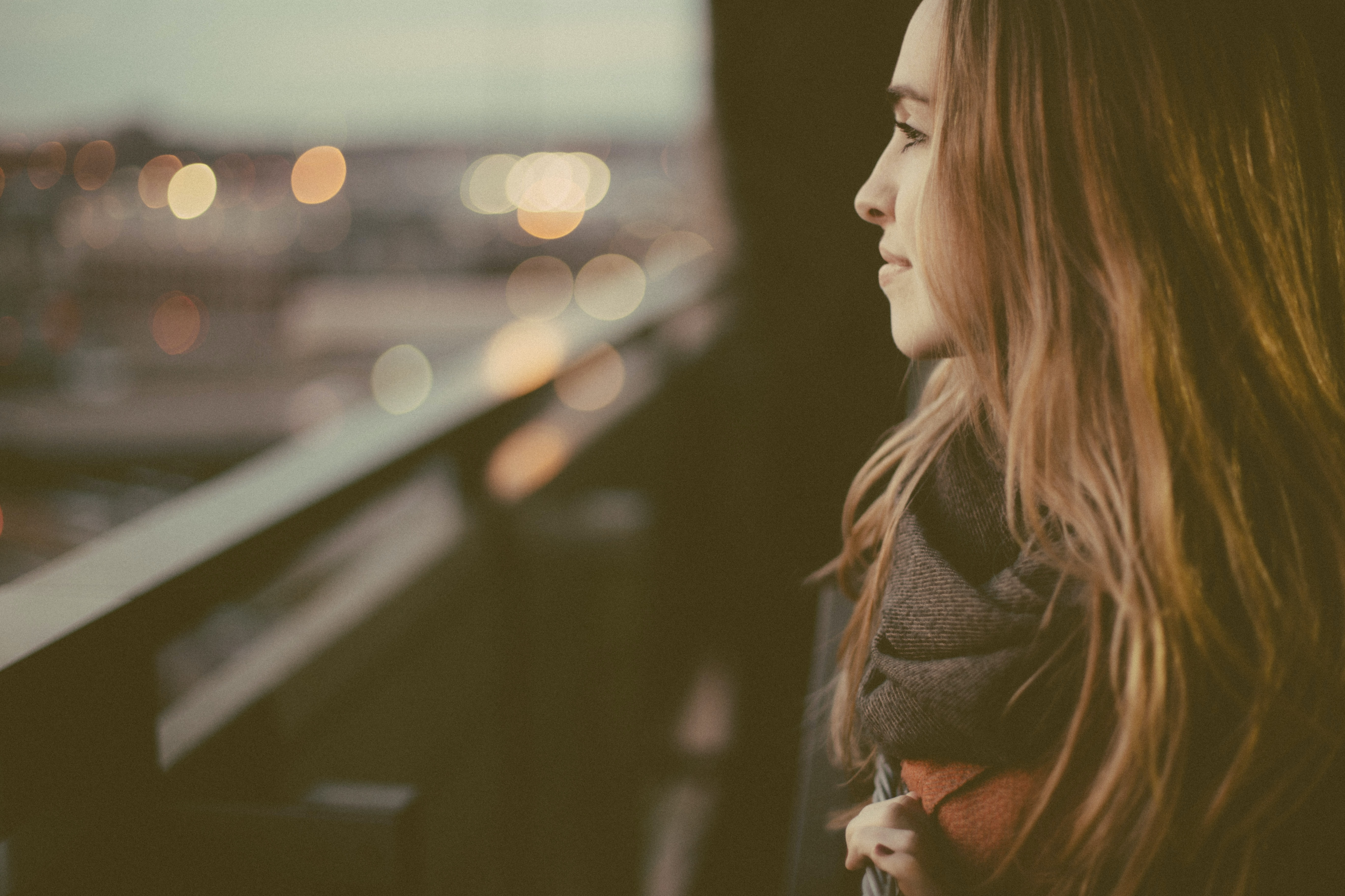A young woman in a scarf smiling when looking off into the city from a balcony