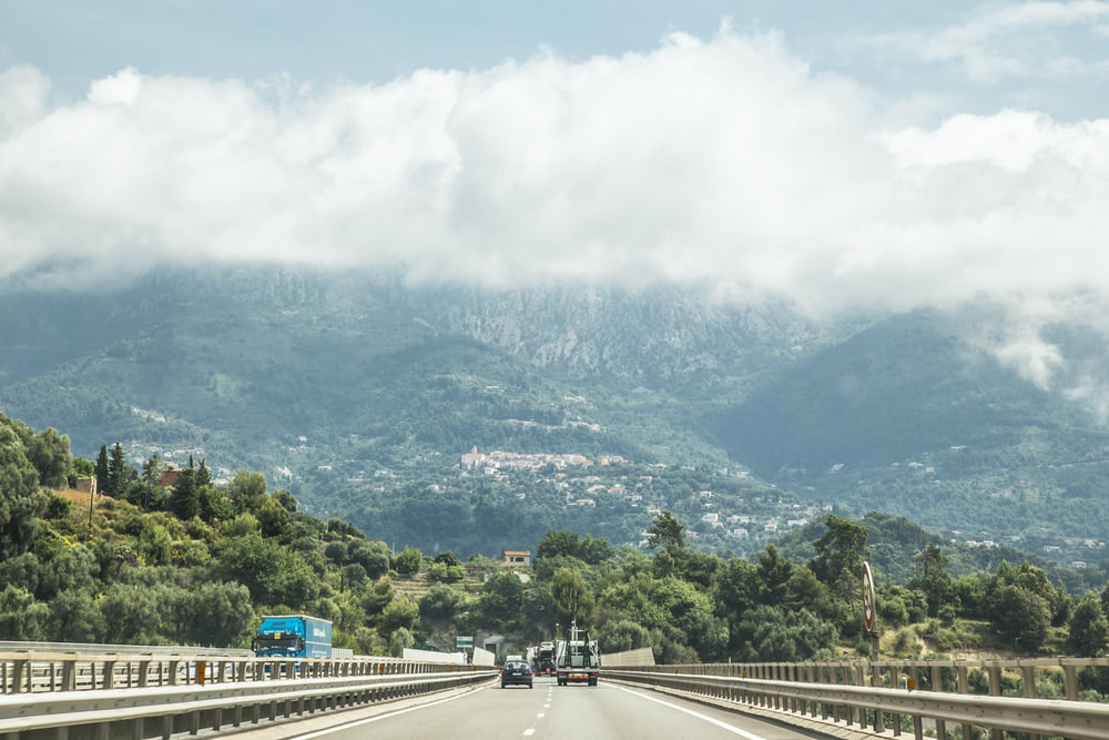 people walking on road near green mountains during daytime