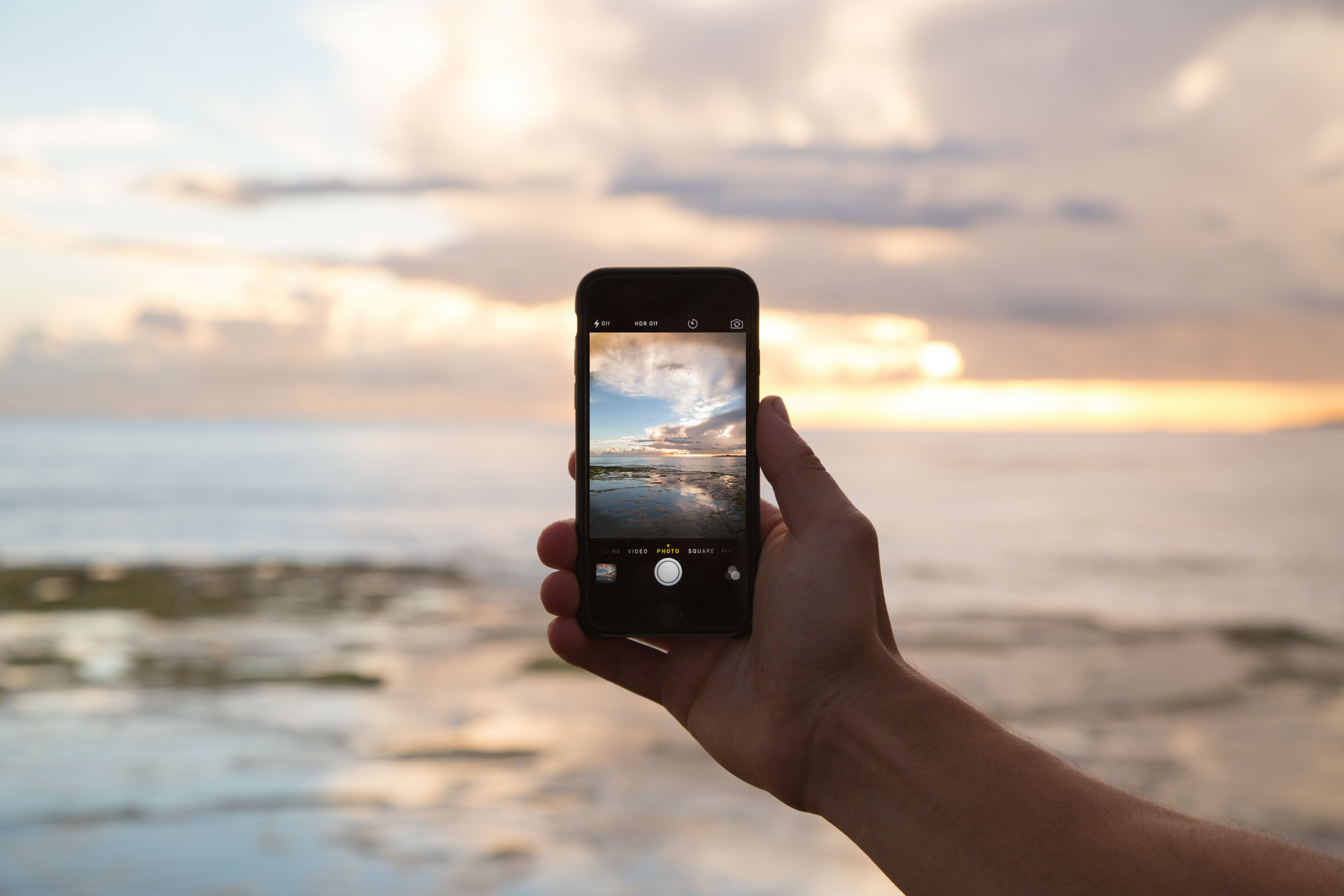 A hand holding out an iphone for a landscape picture of the evening sky and the setting sun