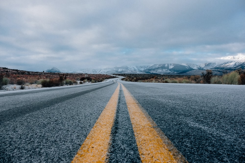 landscape photography of asphalt road under cloudy sky during daytime