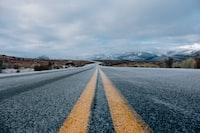 landscape photography of asphalt road under cloudy sky during daytime