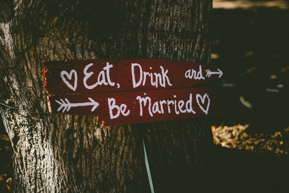 red and white eat, drink, and be married signage near brown tree