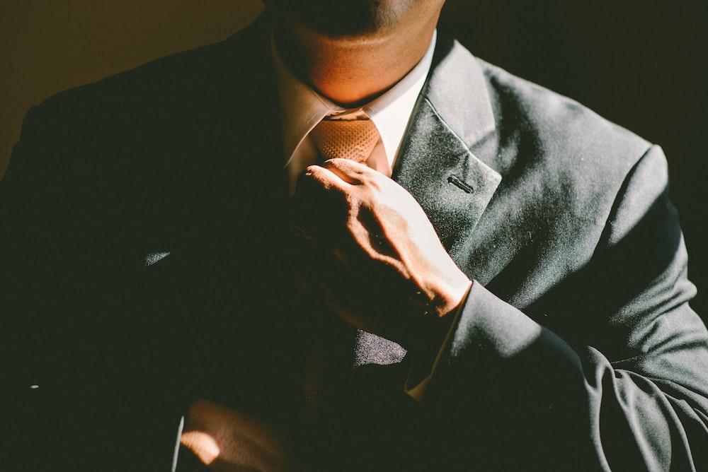 黒いスーツを着た男がネクタイを緩める