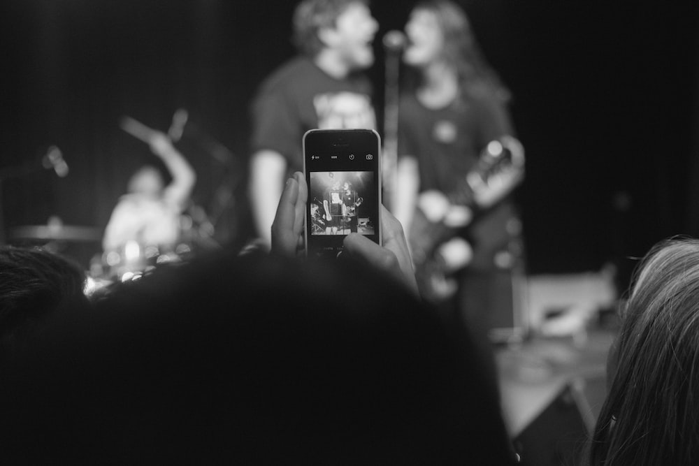 grayscale photo of woman taking photo of people