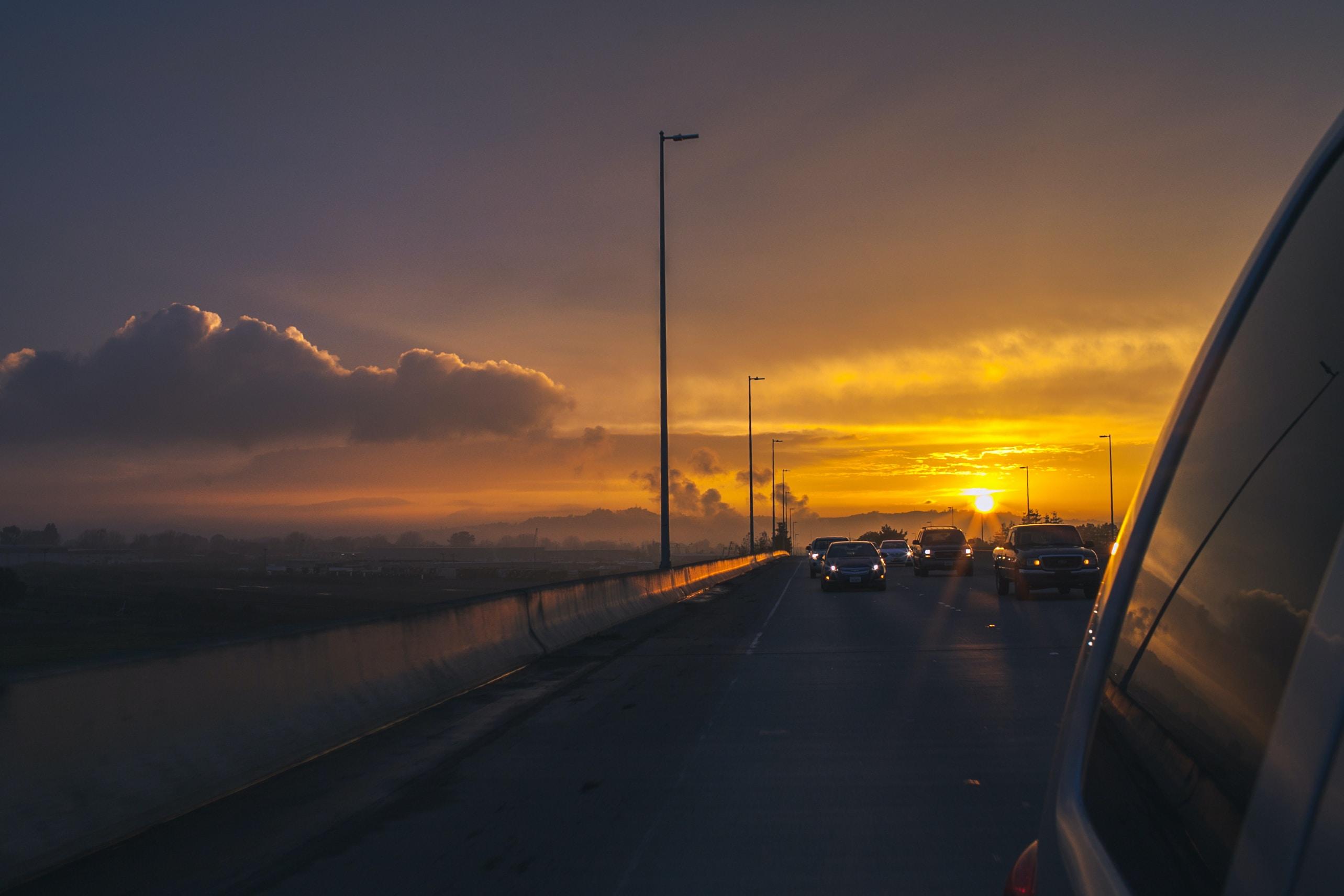 Sun sets behind a car in freeway traffic.