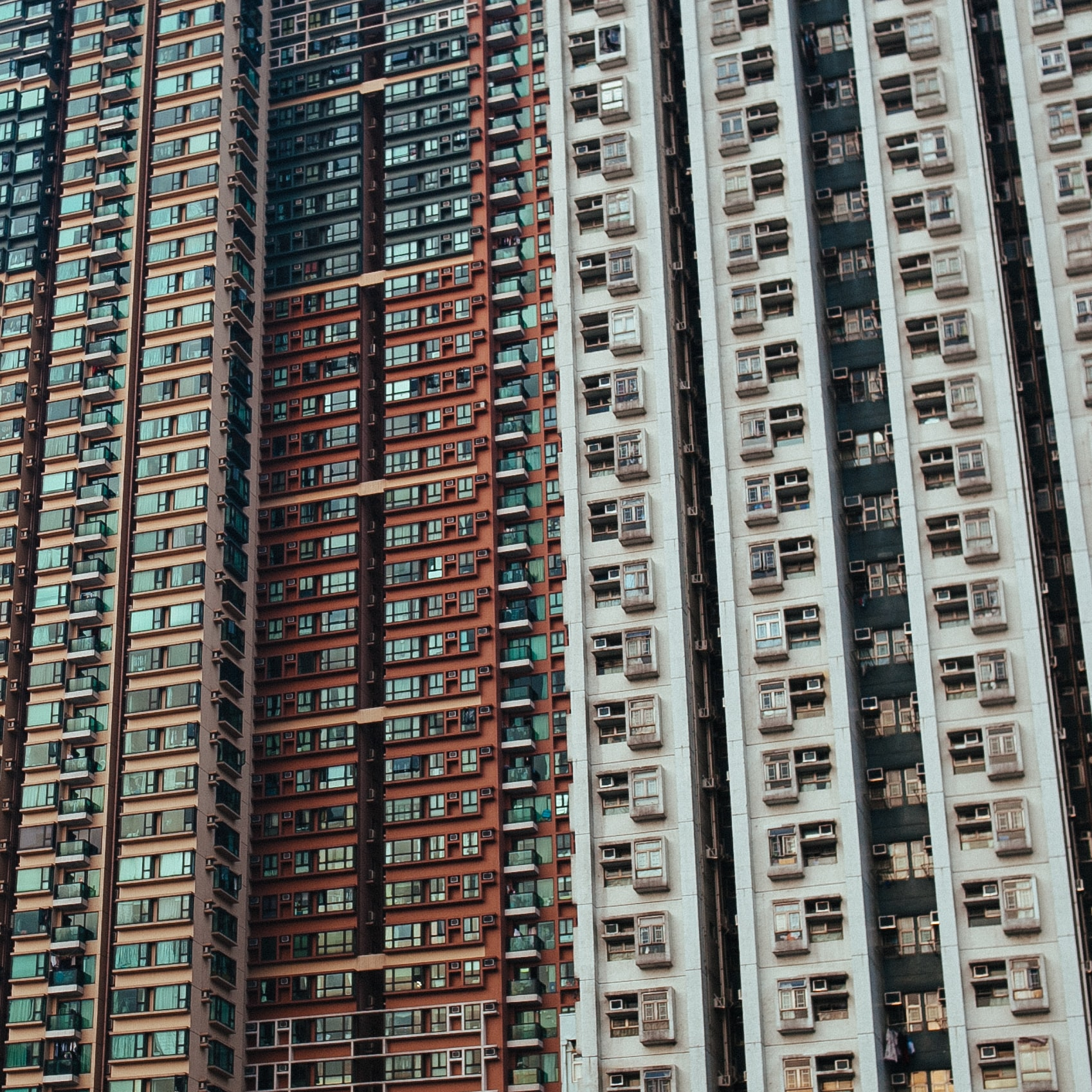 Long shot of multi-colored high rise apartment buildings with windows