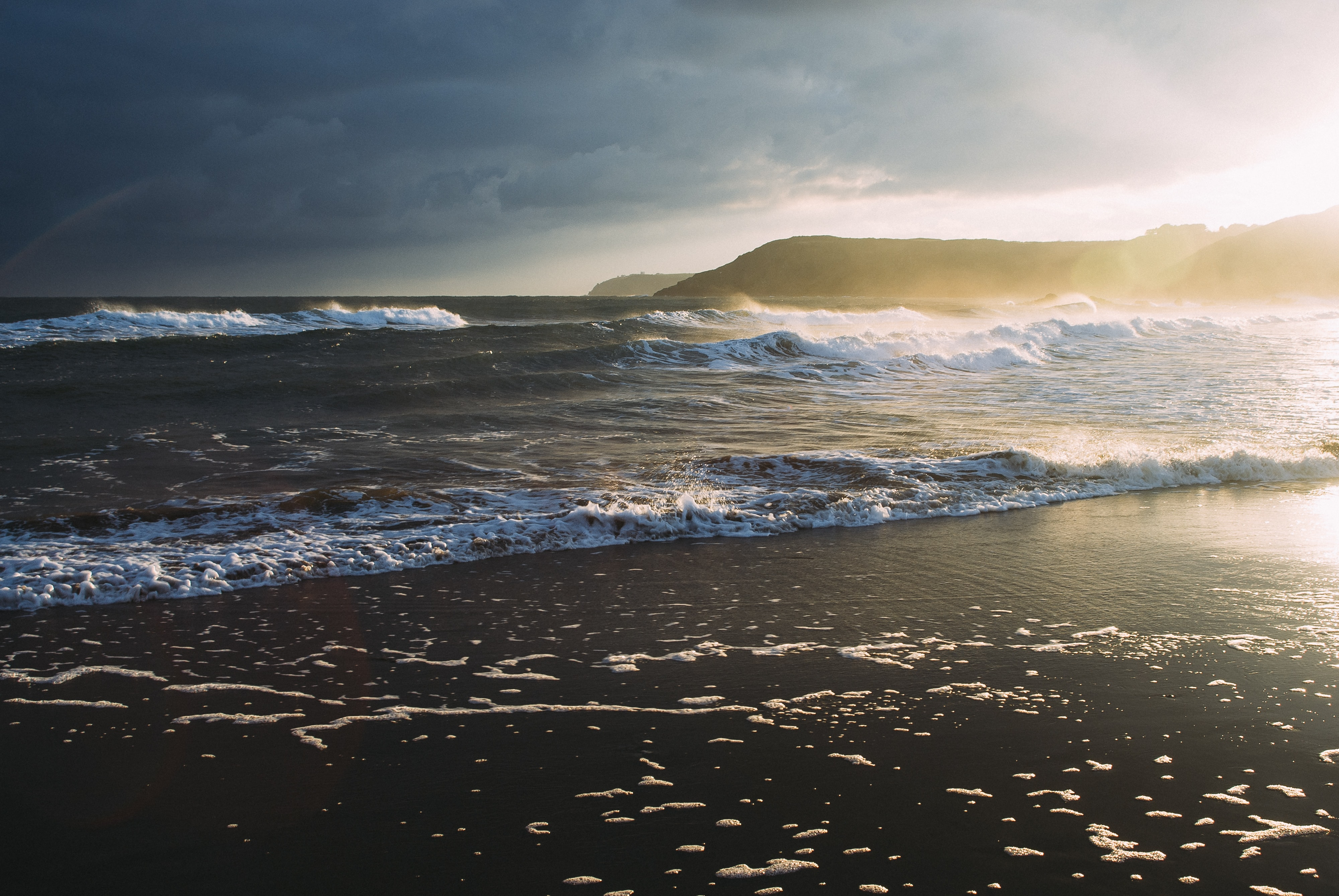 High wave ocean washing on to seashore at beach with looming sunrise