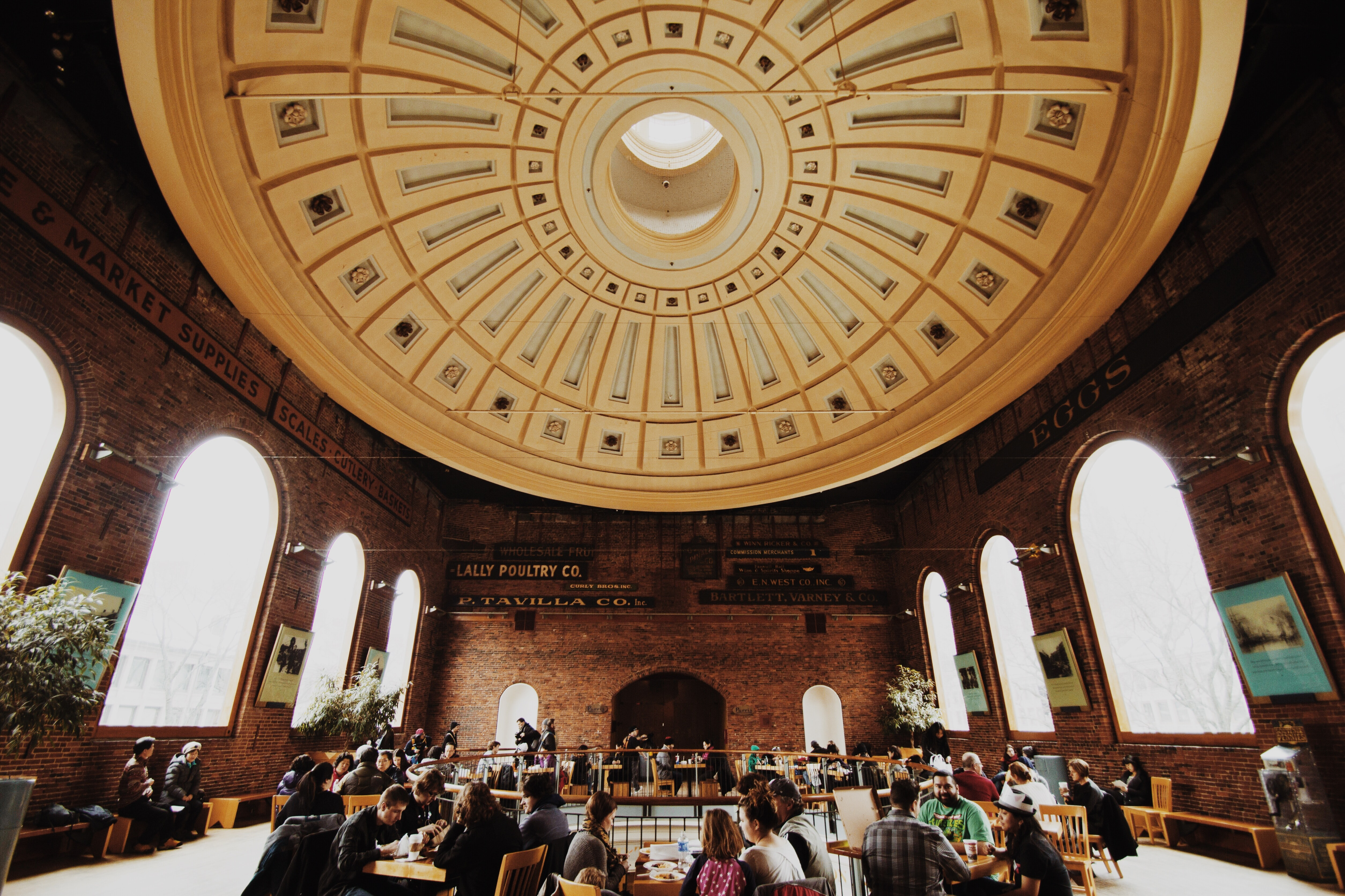 People eating at tables in a brick building with an impressive dome