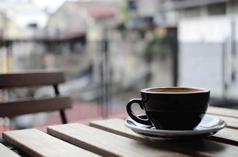 selective focus photography of black ceramic tea mug and plate on brown wooden table during daytime