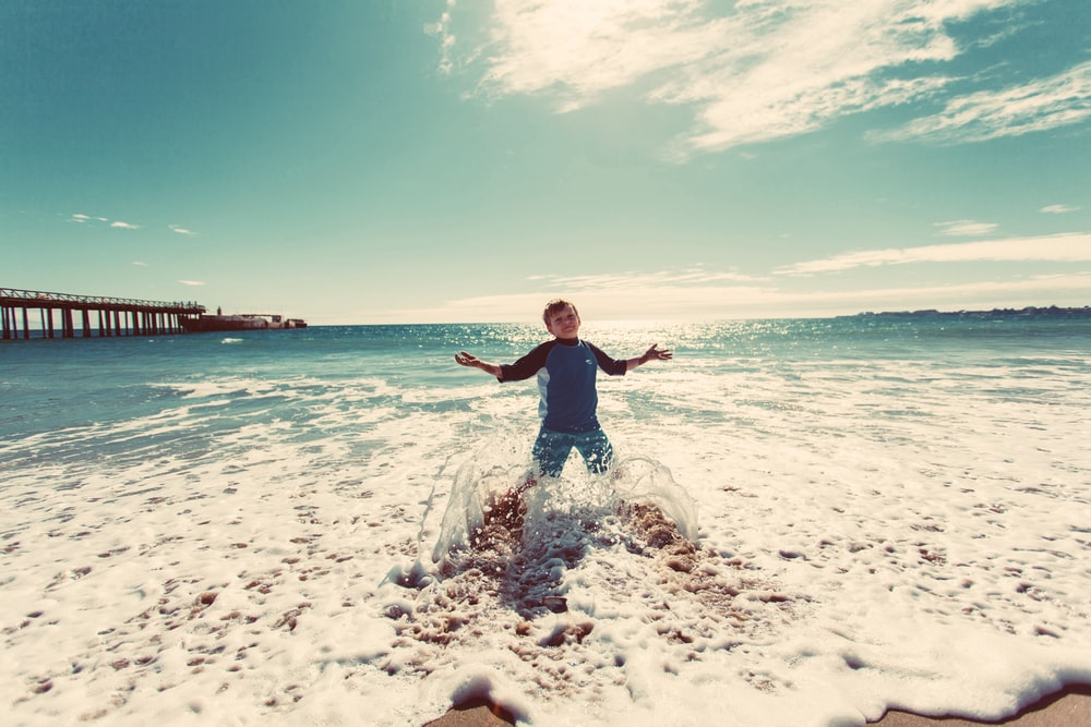 boy playing on shore under blue sky during daytime