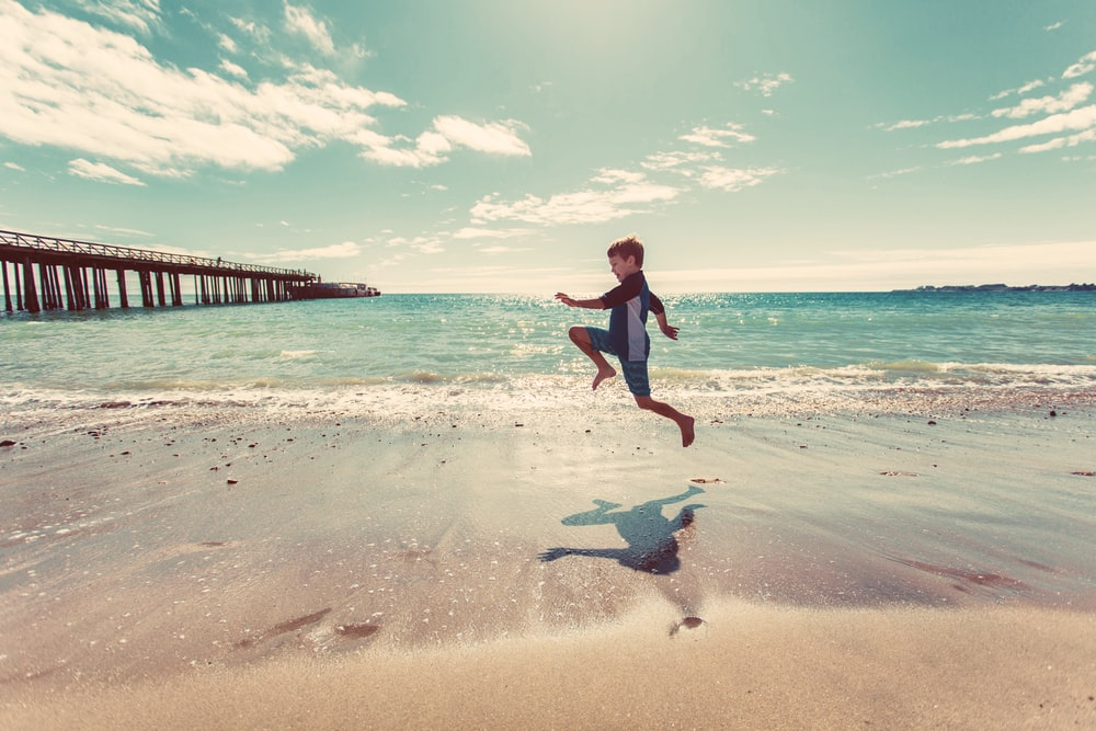 boy in wetsuit jumping on shore
