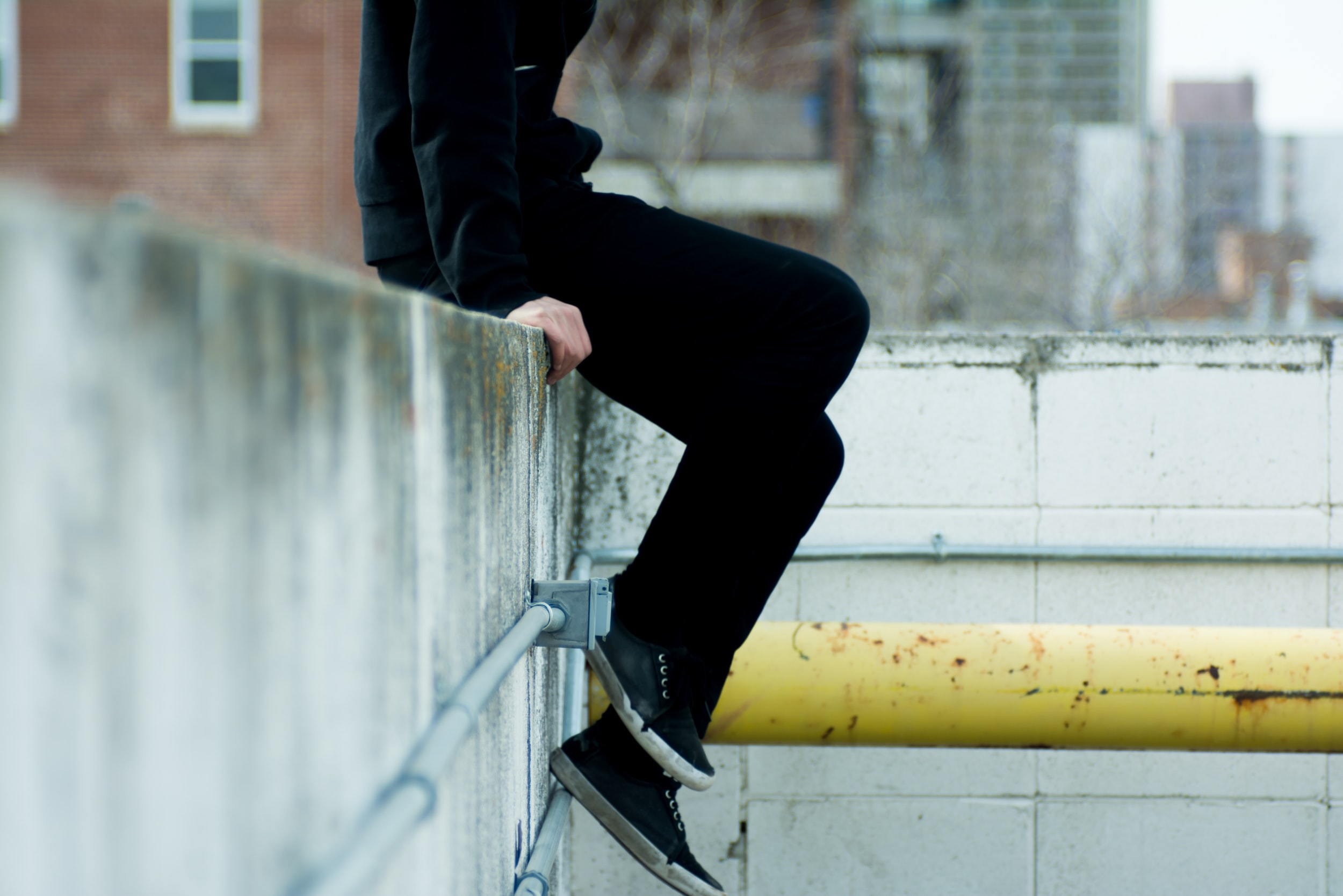 person sitting on top of white concrete wall near yellow metal pipe