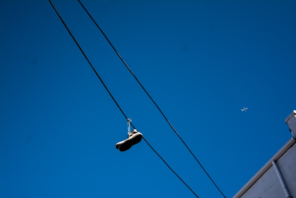 unpaired shoe hanging on cable
