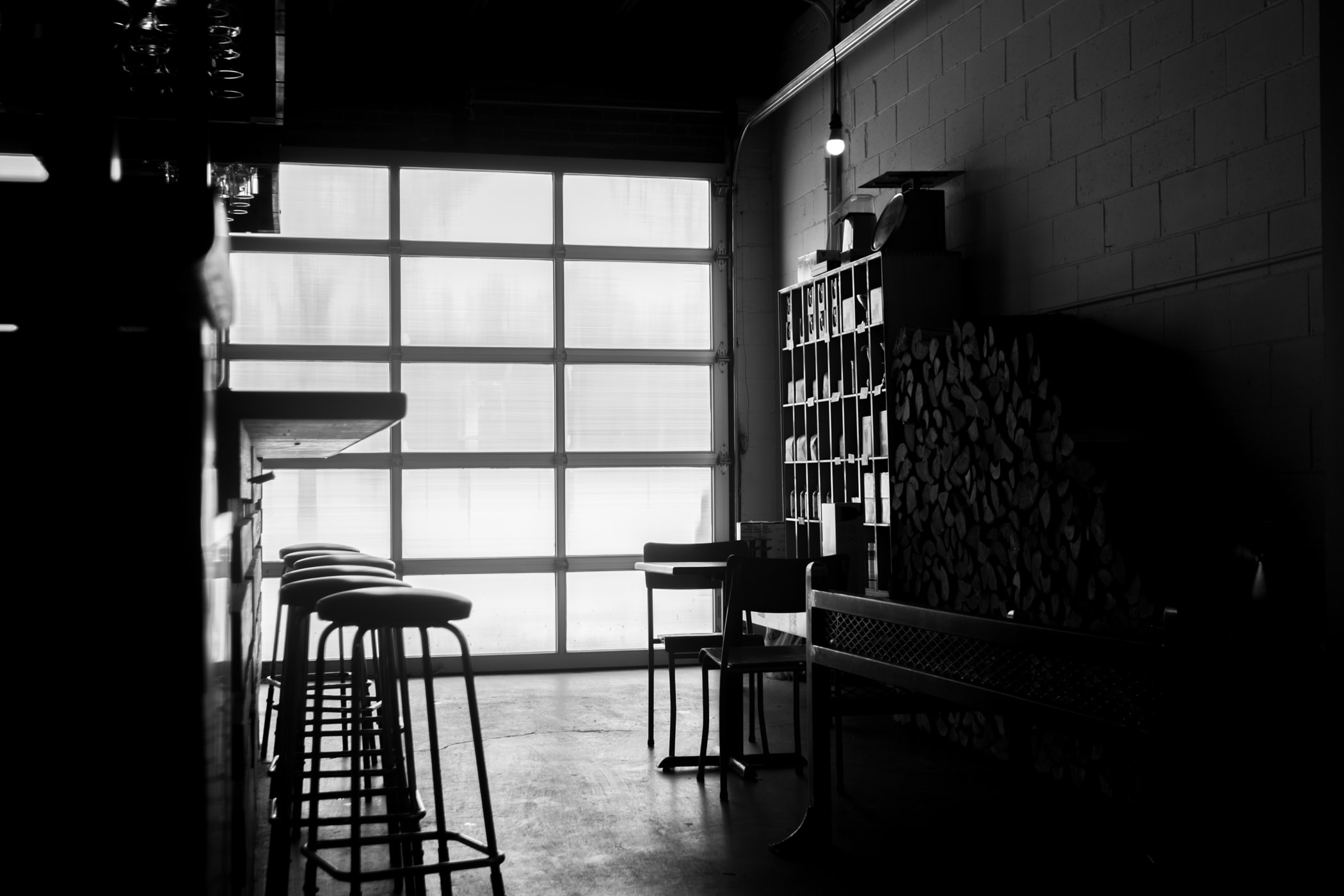 Black and white shot of restaurant interior with stools, counter and big wall window