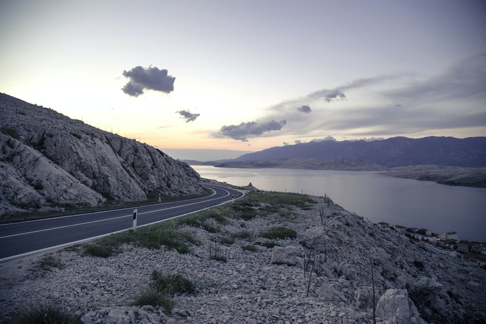 gray concrete road near body of water during daytime